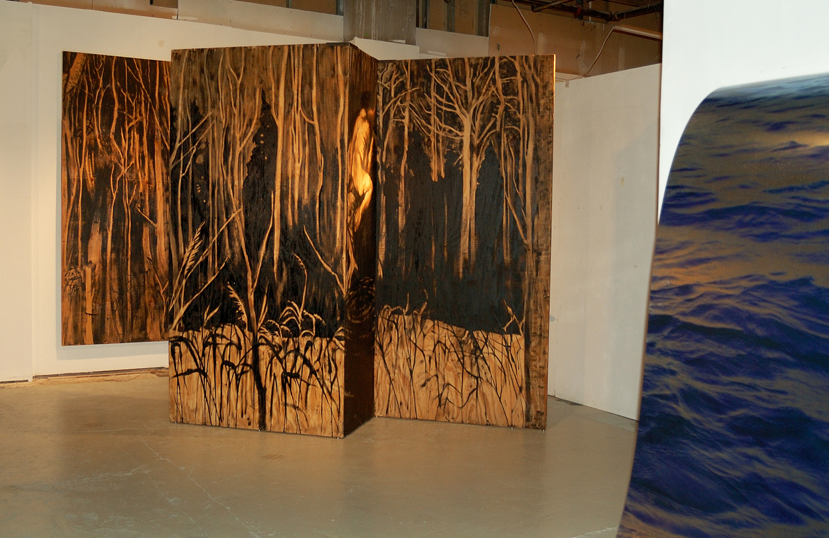 """Living Room"" was a one-person show at Gallery 13, 811 LaSalle St., Minneapolis, MN.  The animals are life-size, Corten steel, the panels, both freestanding  and wall-hung, are each 4' x 8' plywood, painted in asphaltum. Another component of ""Living Room"" was a group of Lake Superior water images printed on steel, glimpsed here."