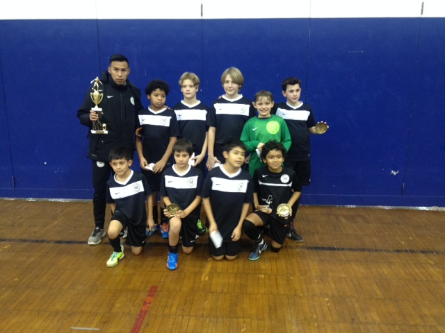 Met Oval players and coach showing off one of a host of trophies racked up this winter by Met Oval teams while working through a futsal winter training schedule.