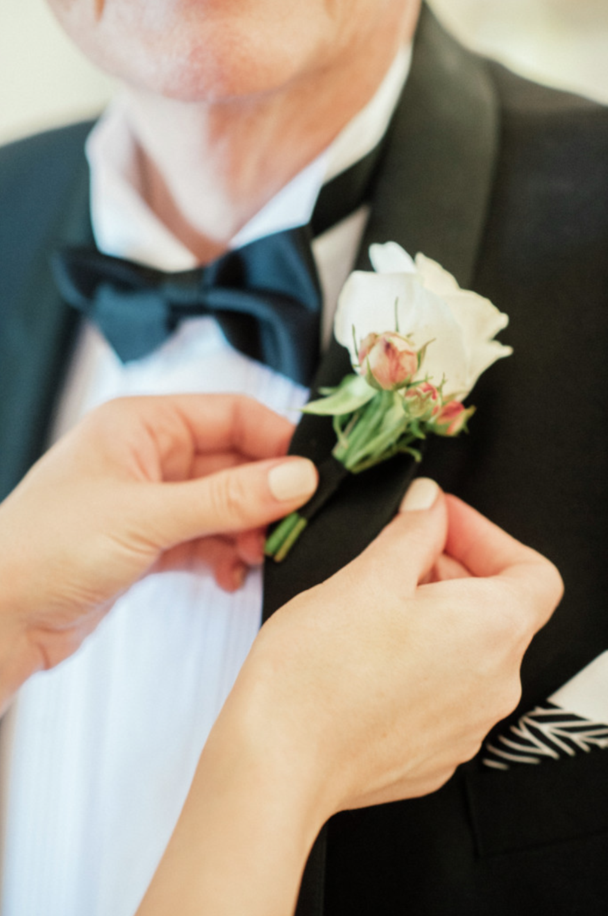 Bride pins flowers to father