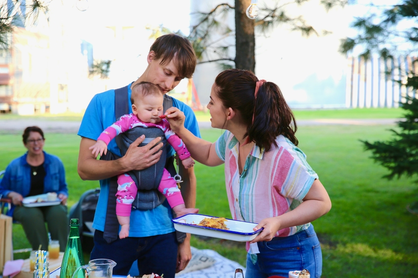 Molly helps Nick prep a plate to eat while he carries their baby .jpeg
