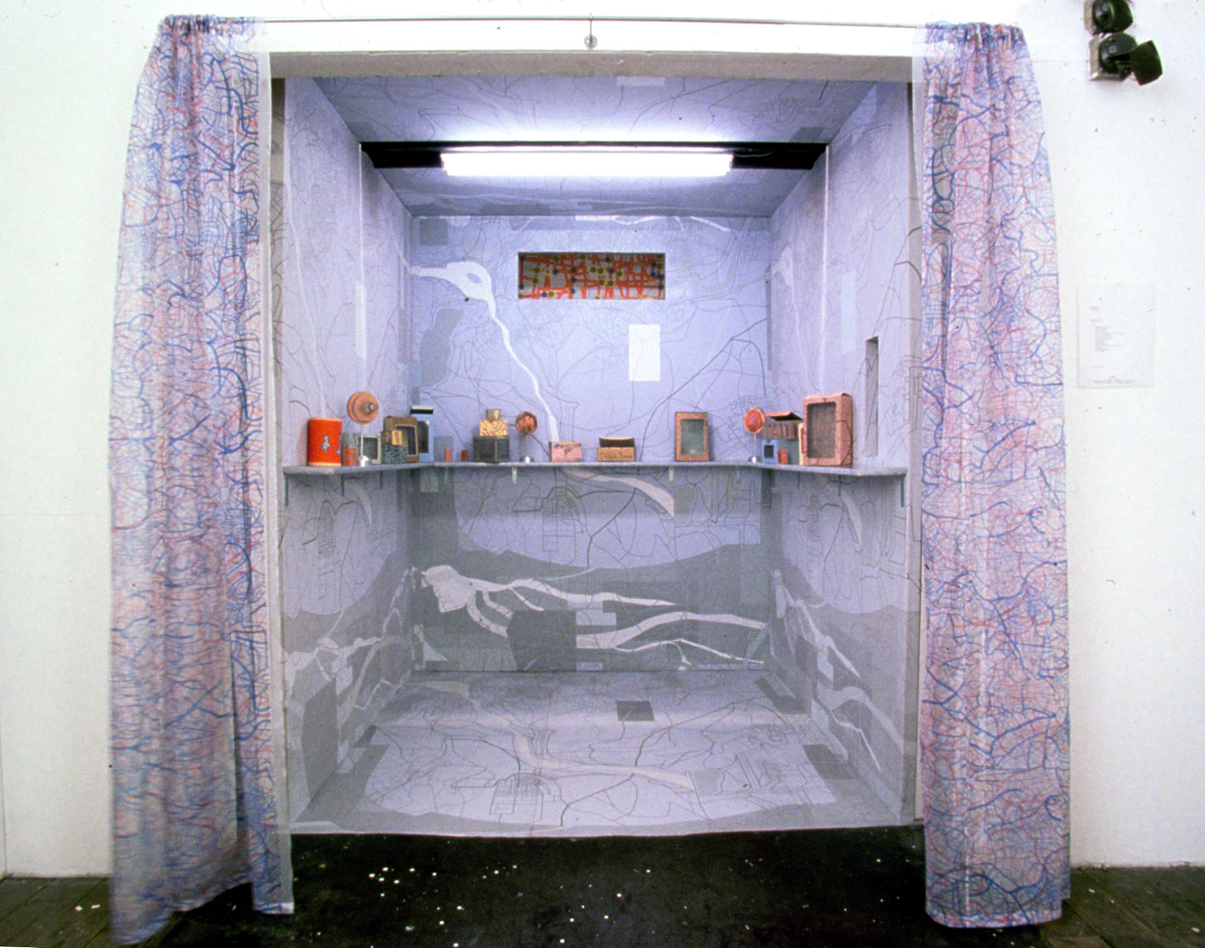 "2 Standard Stops. 1998  Working elevator, between two floors. Digital printing on paper mounted to plywood box built into elevator. Shelf laminated with digital prints, fictional product boxes (digitally printed, hand made) and, ""navigation"" objects"" (machined aluminum + digital print on laser cut plexi). Screen printed silk curtains, fluorescent light."