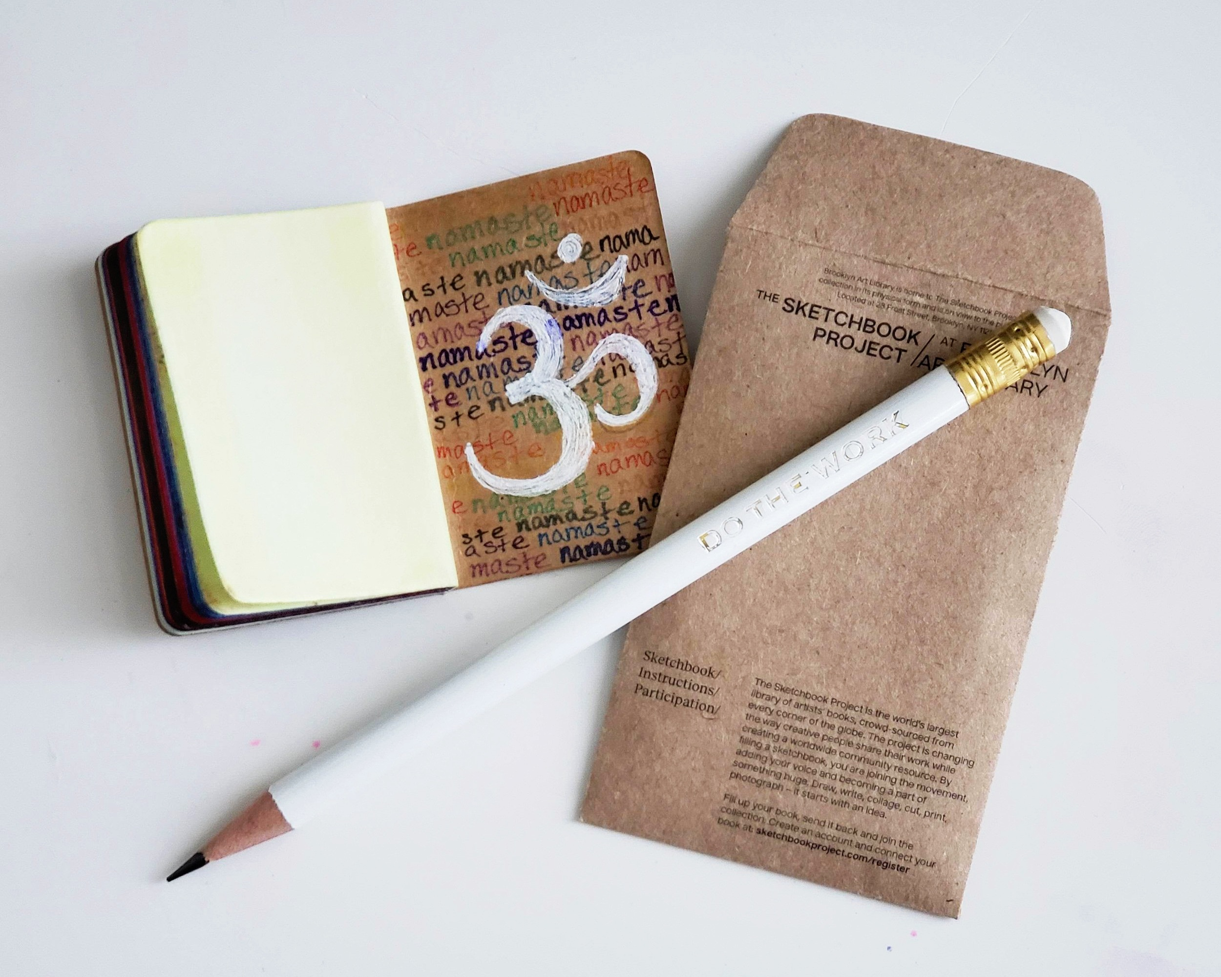 A finished Tiny Sketchbook next to it's mailer and a Do the Work motto pencil from Thrive Art Studios.