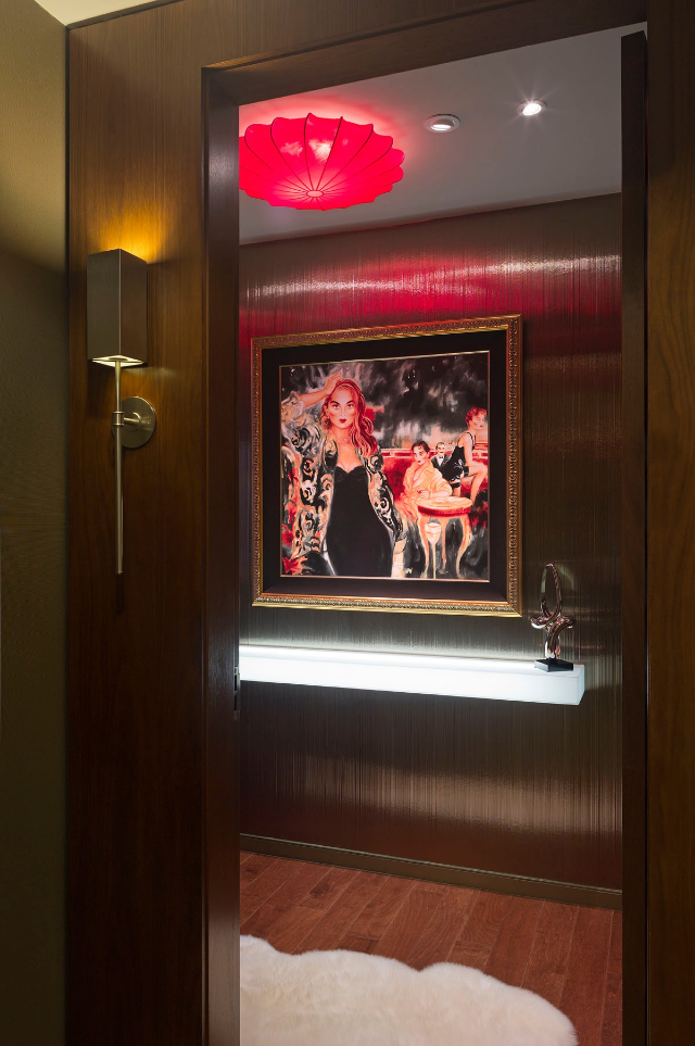 This dramatic entry is unforgettable with four layers of light: dimmable recessed lights, scarlet ceiling fixture, illuminated wall shelf, and modern bronze wall sconce.