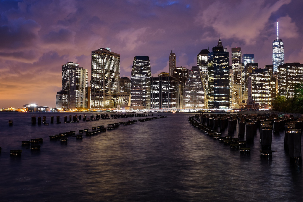 """Stormy Sunset in New York"", October 2014, Brooklyn, New York   Fujifilm X100s, 23mm, f/5.6, 2.6 sec, ISO 500   I've probably taken this shot of lower Manhattan from Brooklyn Bridge Park fifty times now. This one stands out for me, not just because of the amazing sky, but because of the way the metal bands on the tops of the pylons reflect the streetlights behind me. Usually, these poles either fall completely in shadow (like  this ), or are partially lit and a bit distracting (like  this ). But on this night, some alchemy of lights, angle and camera settings came together to give each silhouetted pylon a shimmering halo, mirroring the bands of lights along the skyline."