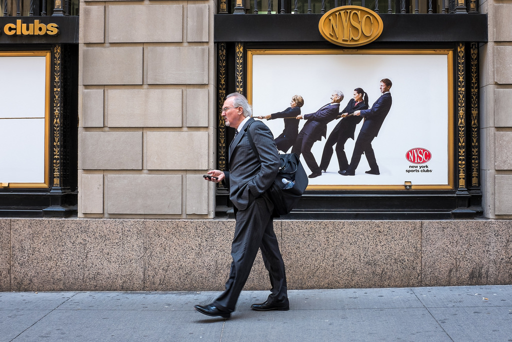 """Wall Street""  May 2014  , New York City  Fujifilm X100s, 23mm, f/5.6, 1/150, ISO 800   I took this photo on Wall Street, a block east of the New York Stock Exchange. While I'd like to tell you that this was a single, serendipitous moment, it didn't quite come together that way. After noticing the poster on the wall and getting the idea for the photo, I went back to this spot for two days in a row trying to capture this image. It must have taken 200 tries before I got one with a single businessman walking in the right direction, looking just the right amount of unhappy,  who was just the right height so the rope would intersect the back of his neck  ,  and frozen at just the right moment so those two inches of rope would actually attach to his collar."