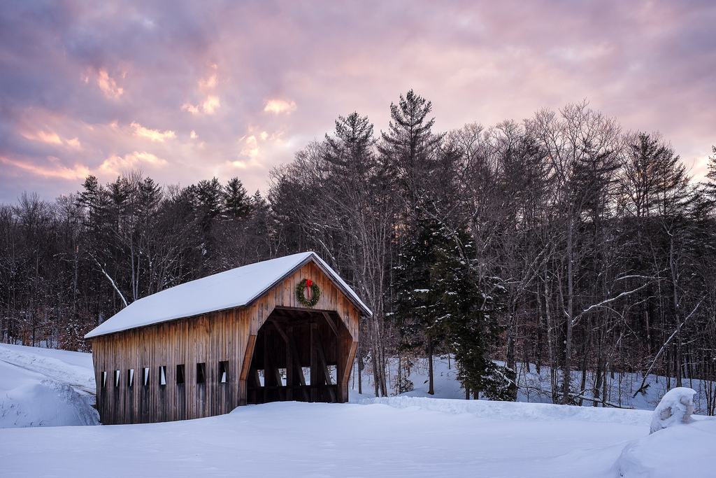 """Covered Bridge at Sunset"" March 2014, South Woodstock, Vermont Fujifilm X100s, 23mm, f/4, 1/80, ISO 250   In March, we planned a long weekend trip to Vermont. Two days before we were scheduled to go, a storm dropped 24 inches of snow across the state. While the snowstorm made for some harrowing driving moments on the less-plowed side roads, it also made for this covered bridge photo op, which is about as iconic Winter-In-Vermont as it gets. Much to my good fortune, they even left their Christmas Wreath up for St Patrick's Day."