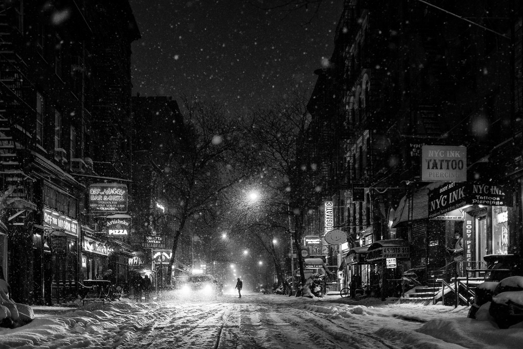 """MacDougal Street Snowstorm"" January, 2014, New York City Fujifilm X100s, 23mm, f/2, 1/125 seconds, ISO 2500   This year was one of the  ten snowiest winters  on record for New York City. So there was no shortage of picturesque snowglobe-quality photo opportunities. But of all the winter photos that I took this year, this shot from Greenwich Village is my favorite. I took this photo while kneeling in the center of MacDougal Street. I snapped a few shots, played around with settings, and tried to compose something interesting. But then this guy stepped off the curb in the distance and crossed into the middle of street. Sometimes it's that tiniest of details that makes all the difference. The other photos from this series are totally unremarkable. This one is magic."