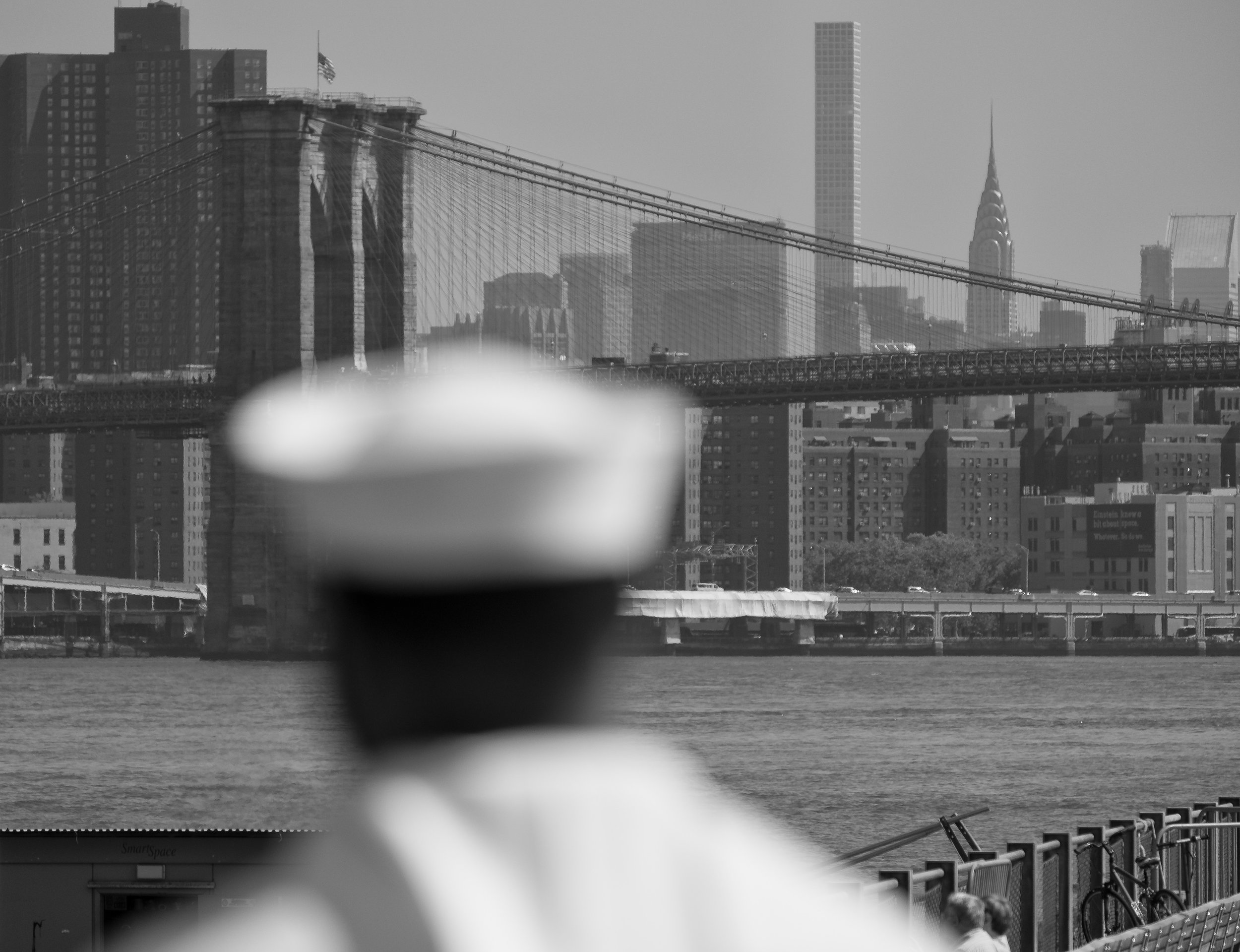 """Fleet week"" May 25, 2018. Brooklyn, New York Fujifilm X Pro2, 55-200mm, f/4.7, 1/1900 sec, ISO 200  Sometimes your camera auto-focuses on the wrong thing and you get really annoyed. Here I was trying to focus on the naval officer and make the city go soft in the background. So I refocused and took that shot next. In this case, my camera was the better photographer."