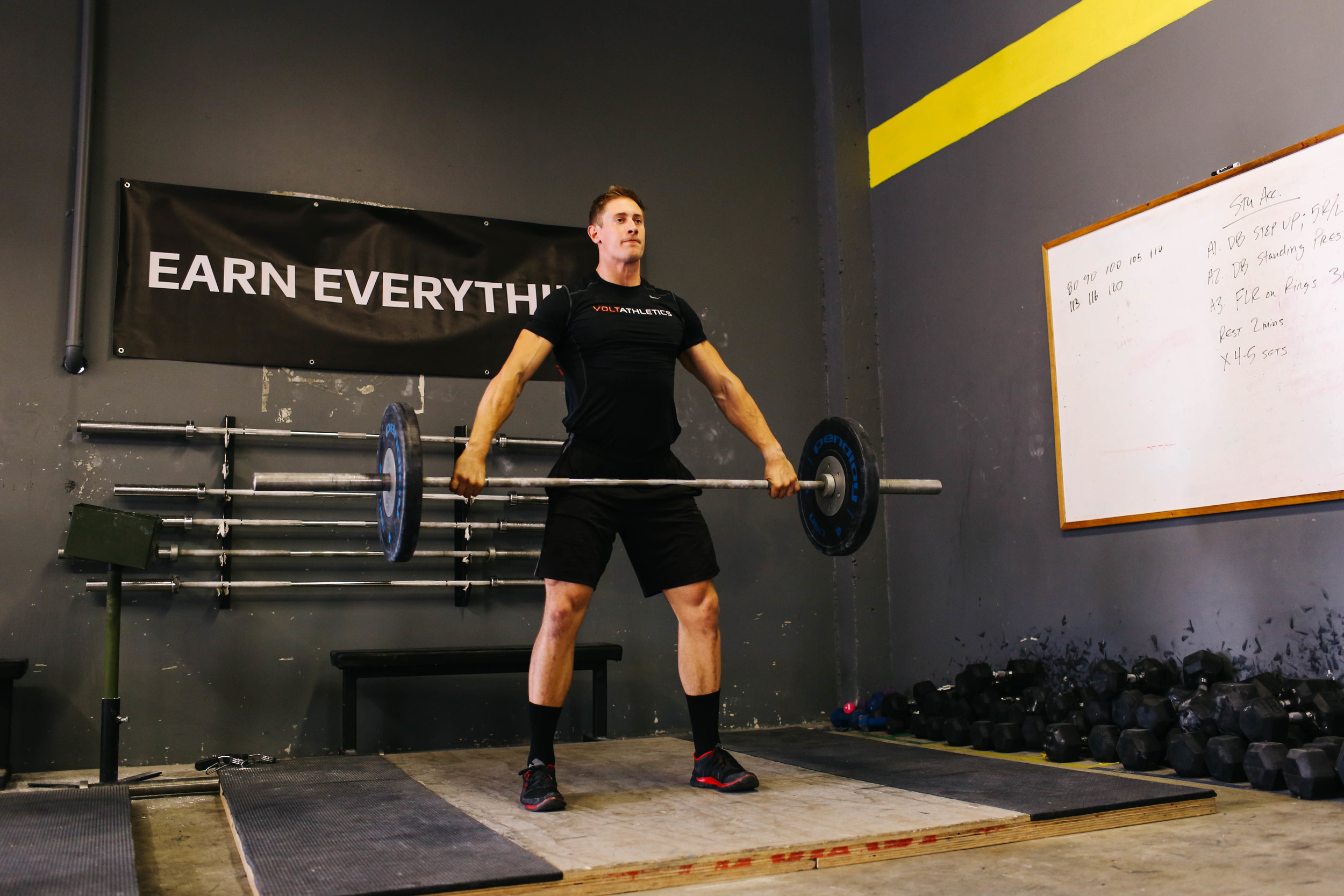 It's more noticeable in a snatch grip, but the lats help to pull the bar into the hip without excessively bending the elbows.