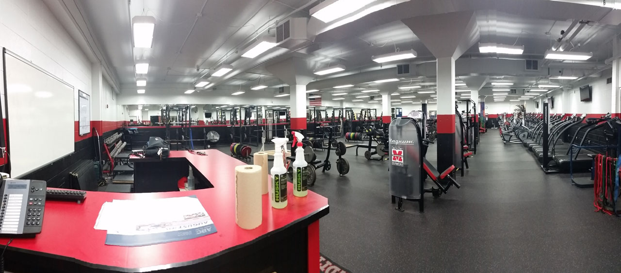 "The new Muskego weight room is all about organization. Students pick up their program in the hall, slap the ""Train Like a Champion"" sign above the door, and check in at the front desk before training. The weight room also contains 4 video cameras to ensure athlete safety (and protect the strength coach from liability) at all times."