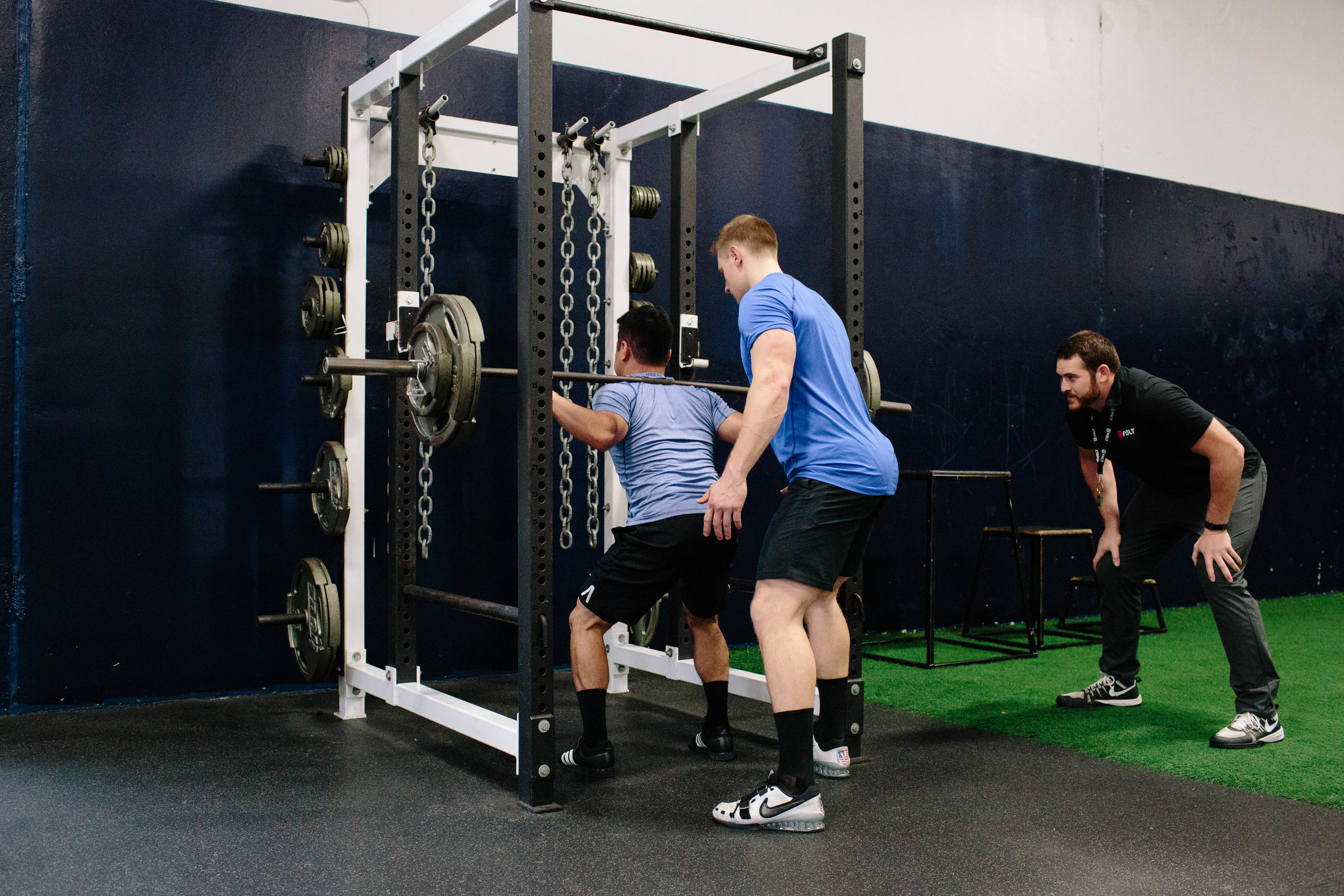 When spotting the squat, the spotter should stand directly behind the athlete and track the movement of the bar with both hands, ready to assist by touching only the weight, if necessary.
