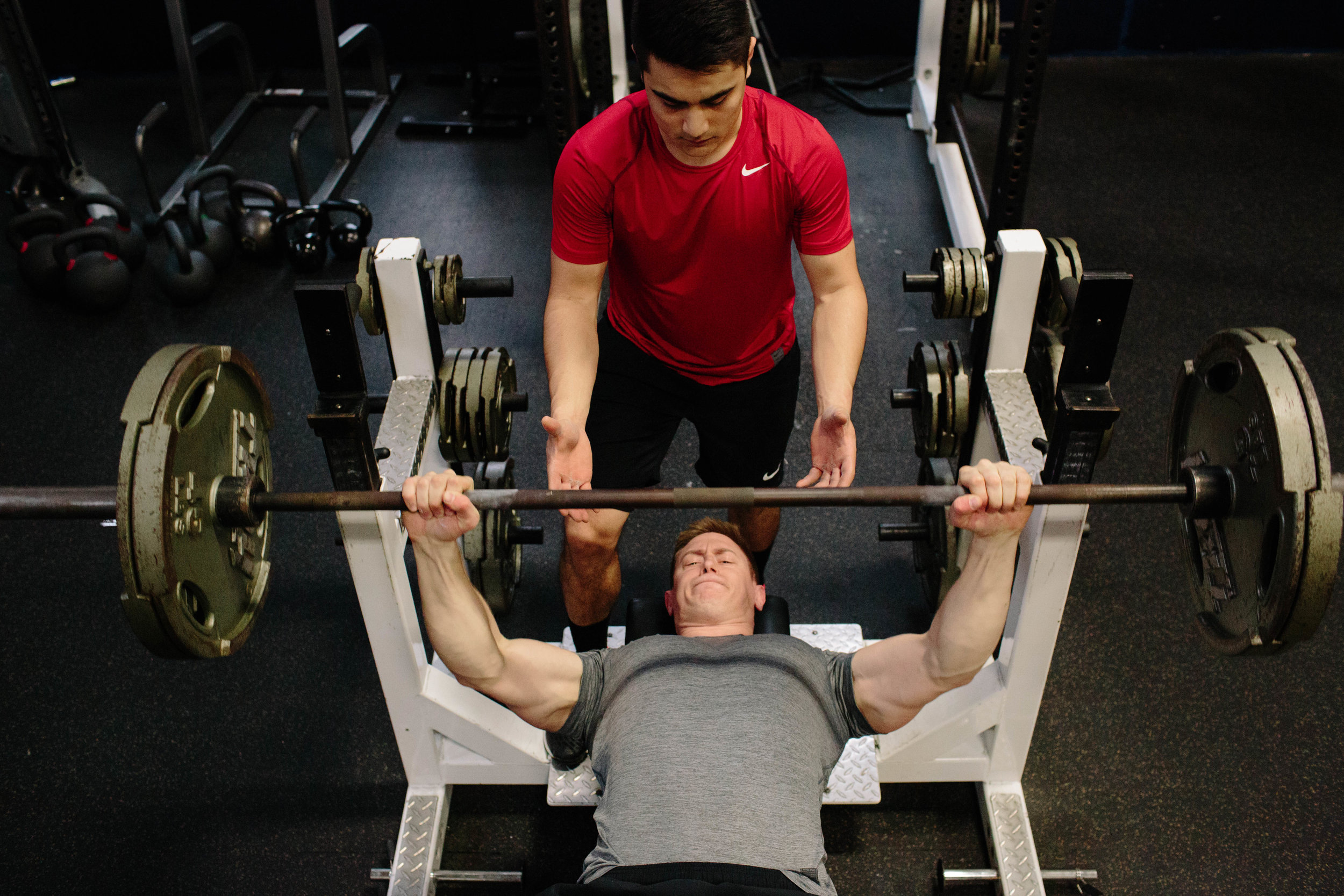When spotting the bench press, the spotter should stand directly behind the athlete's head and help unrack/rack the bar, then track the path of the bar with both hands. Again, the spotter should only assist by touching the bar, not the athlete.