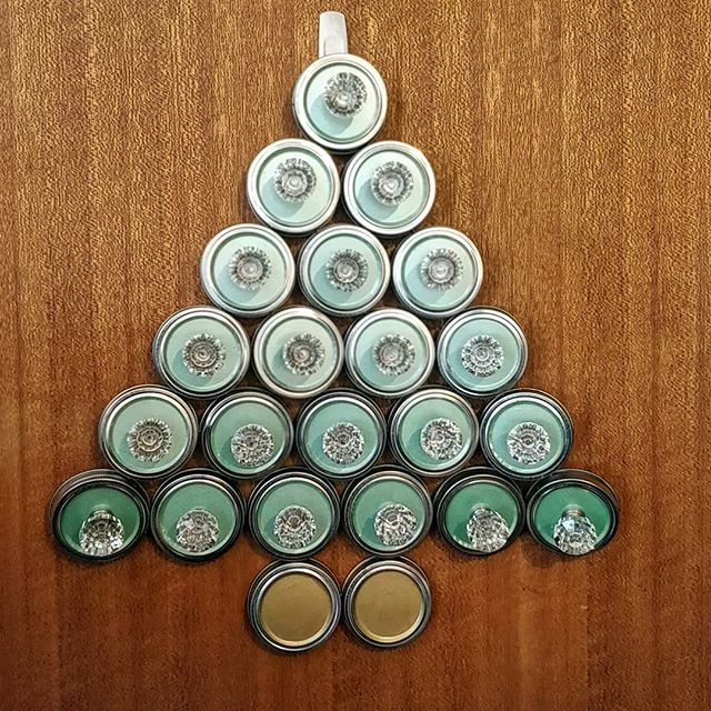 A festive tree made out of mason jar lids and rings with drawer knobs as ornaments.