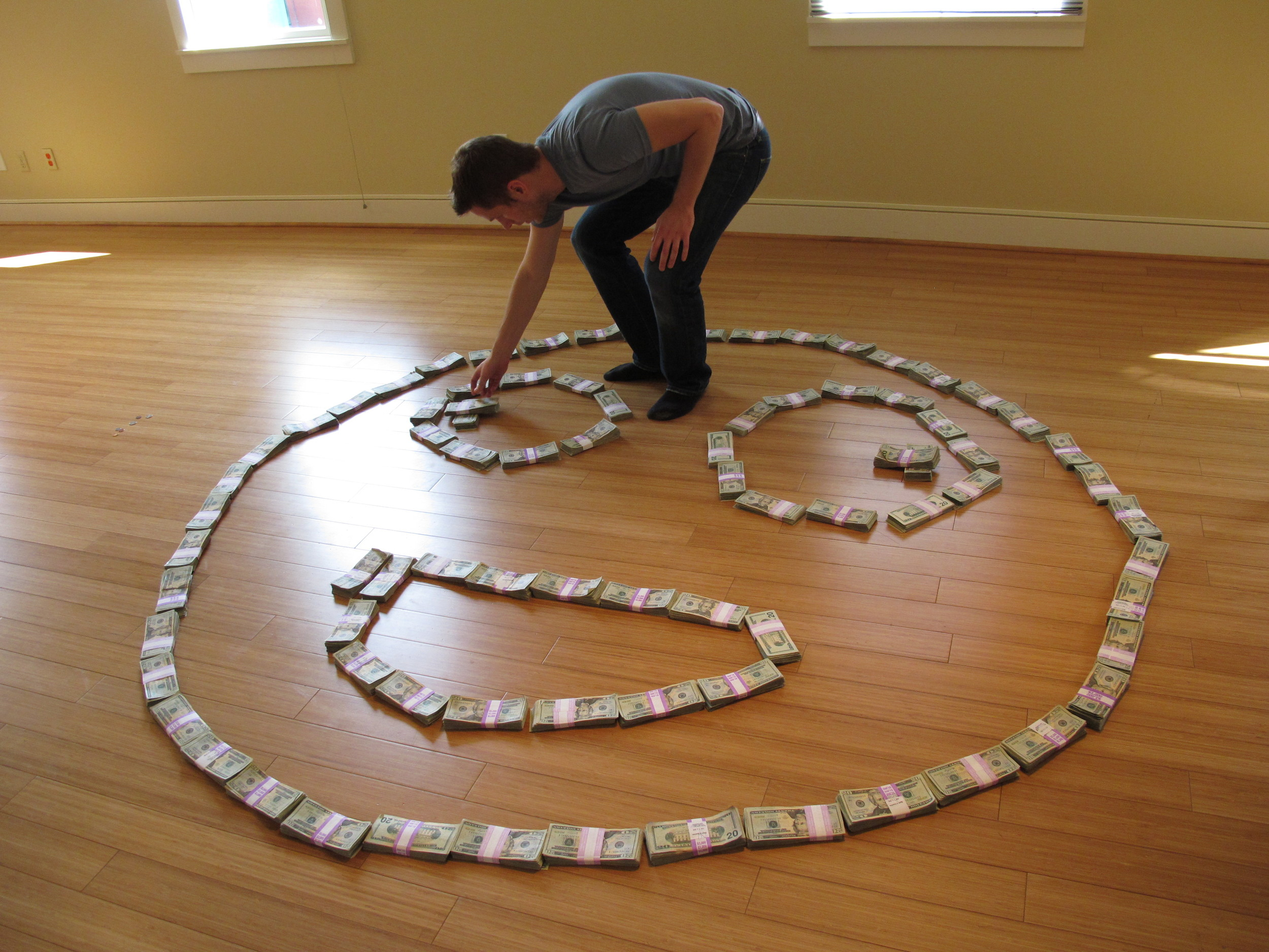 Matthew Inman, the cartoonist behind The Oatmeal, makes a smiley face out of over $200,000 in cash he raised in donations.