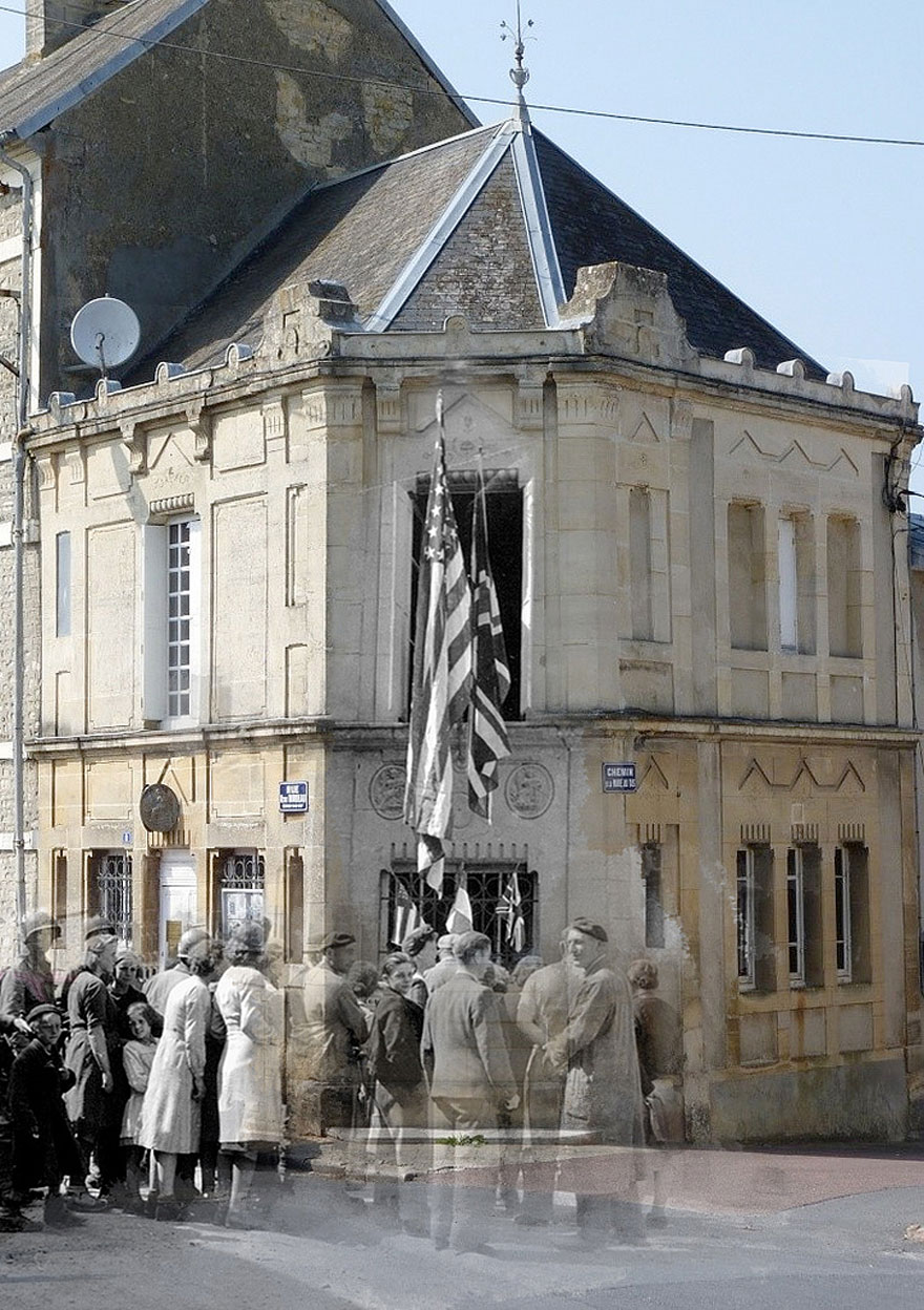 """A group of civilians and GI's in front of the notary office of Trévières Street Octave Mirbeau. The entrance is decorated with French and allied flags."""