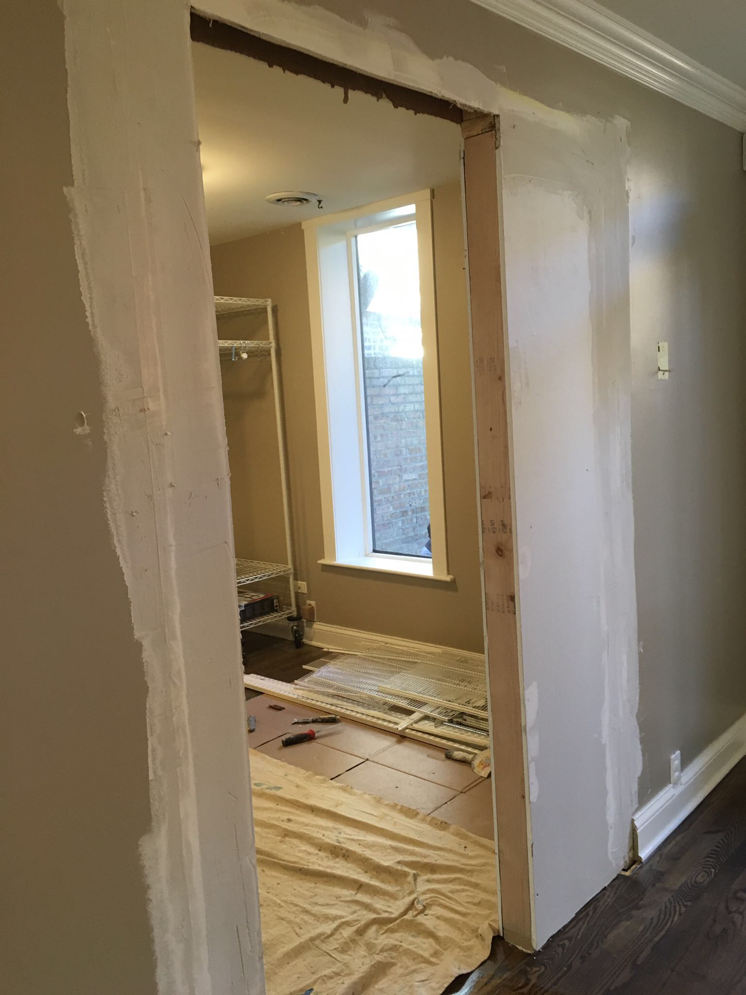 What once housed the odd tri-fold door is now framed and drywalled for a standard size door.