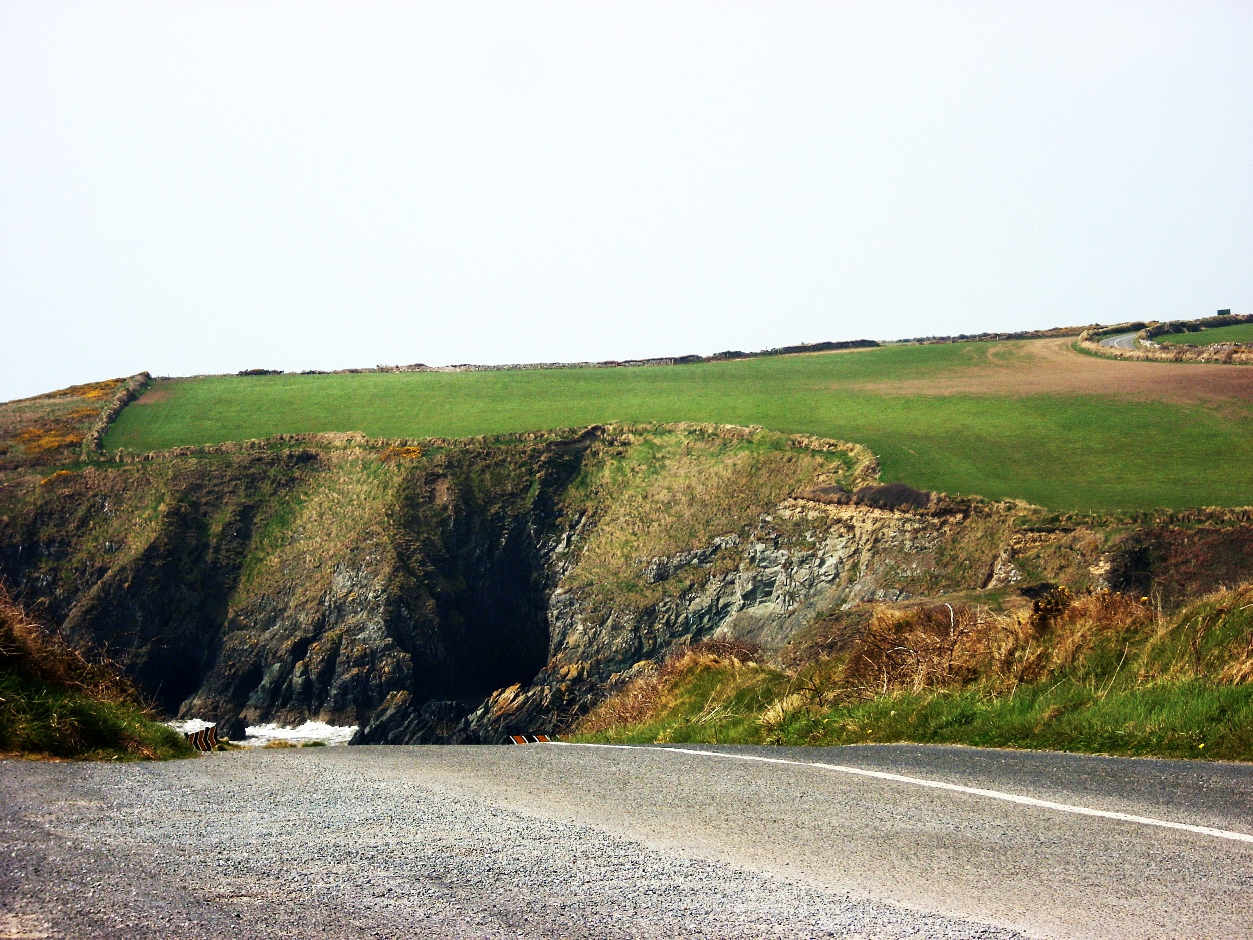 image from the road of green grass and cliffs in county waterford, ireland