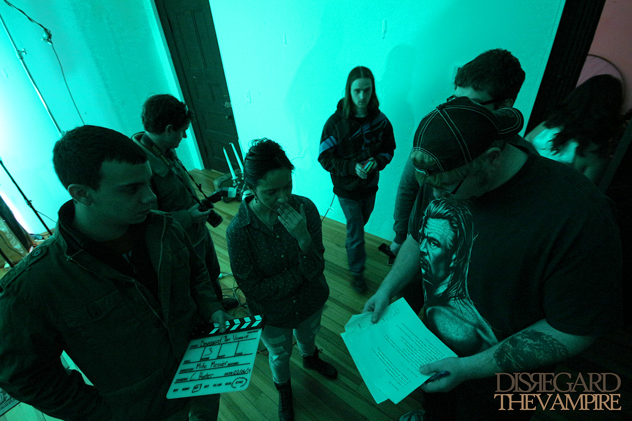 Crew members gather around writer, director and producer Mike Messier to discuss the next scene for Disregard The Vampire, 2014.