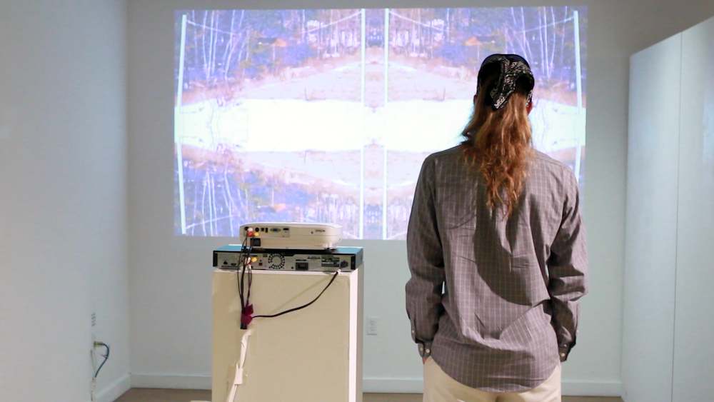 Jeremy Day watches 'Liar Liar, Pants on Fire' at Geena Matuson's (@geenamatuson) TransFIREmation Gallery Show & Installation in the MassArt Student Life Gallery, 2013.