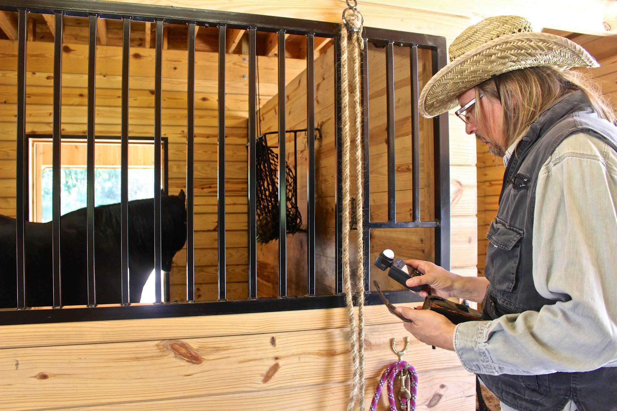 D.P. Luc Nicknair using the light meter in stables, 2014.