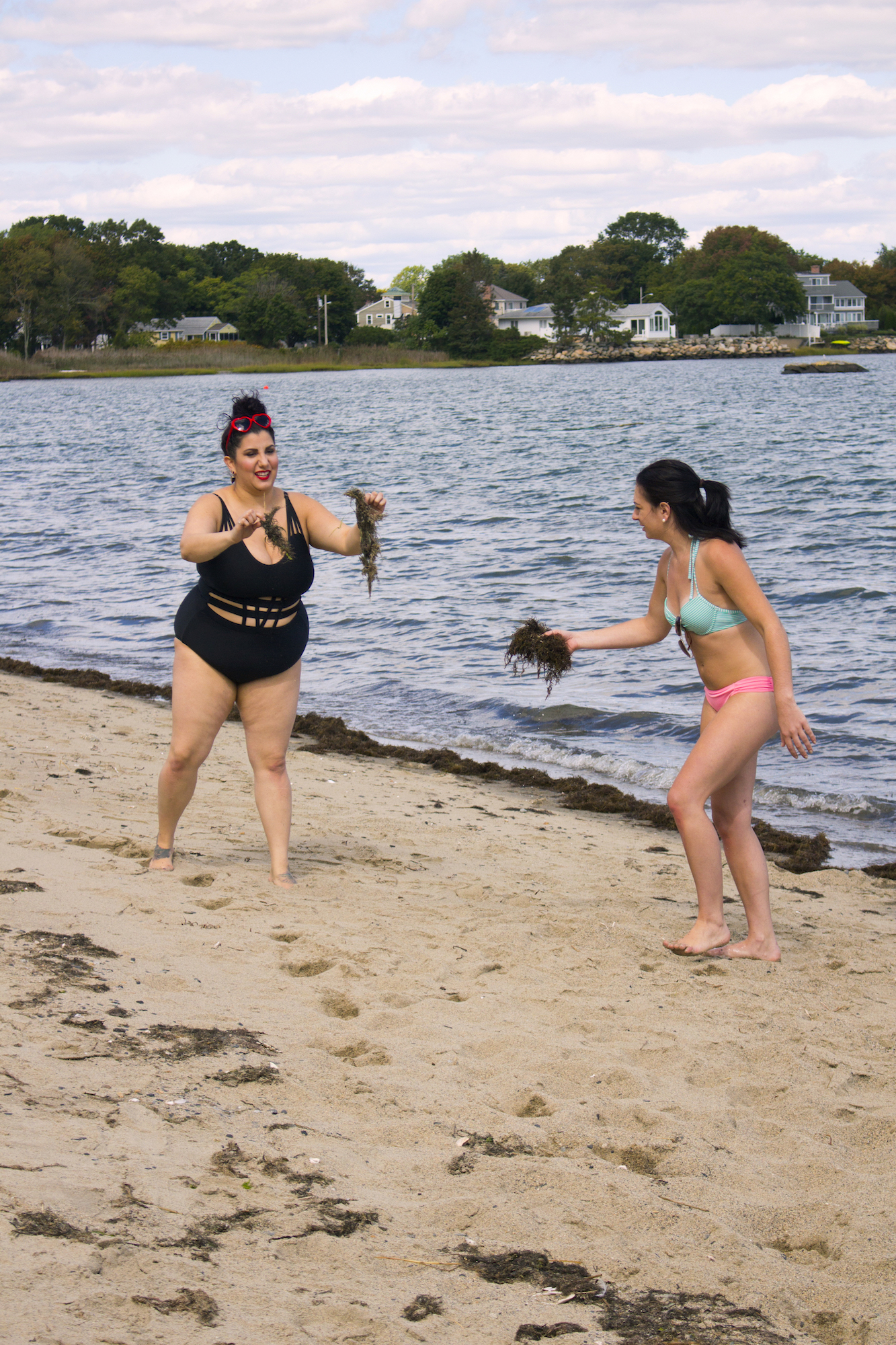 """Actors Alessandra Grima and Catalina Snape collect seaweed with which to """"pamper"""" Geena Matuson on the set of her production for comedic 'beach ads,' part of her 'Fauxmercials' series filming through 2017."""