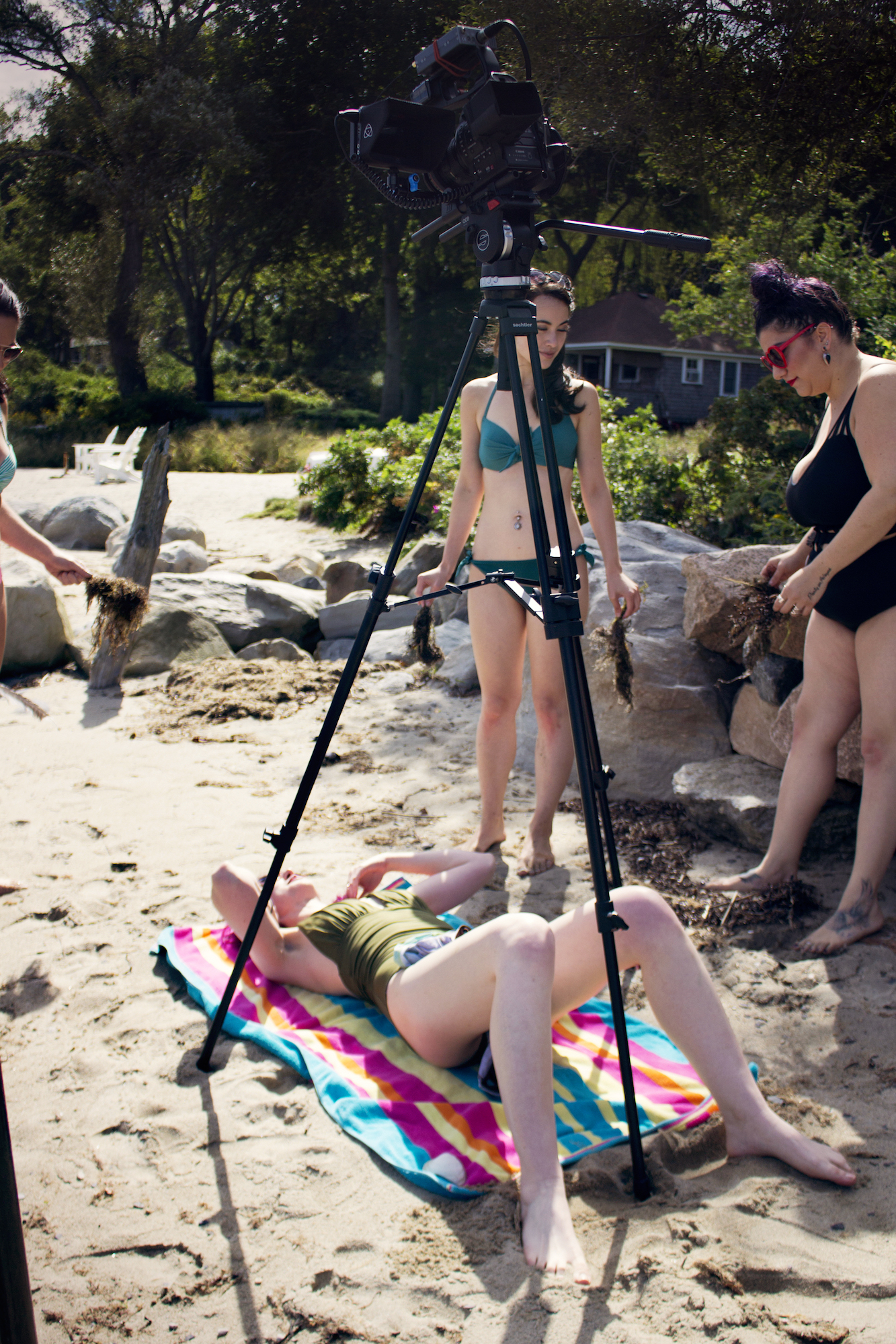"""Actors Maya Simone and Alessandra Grima gather seaweed with which to """"pamper"""" Geena Matuson (on ground) on the set of her 'Fauxmercials' series filming through 2017."""