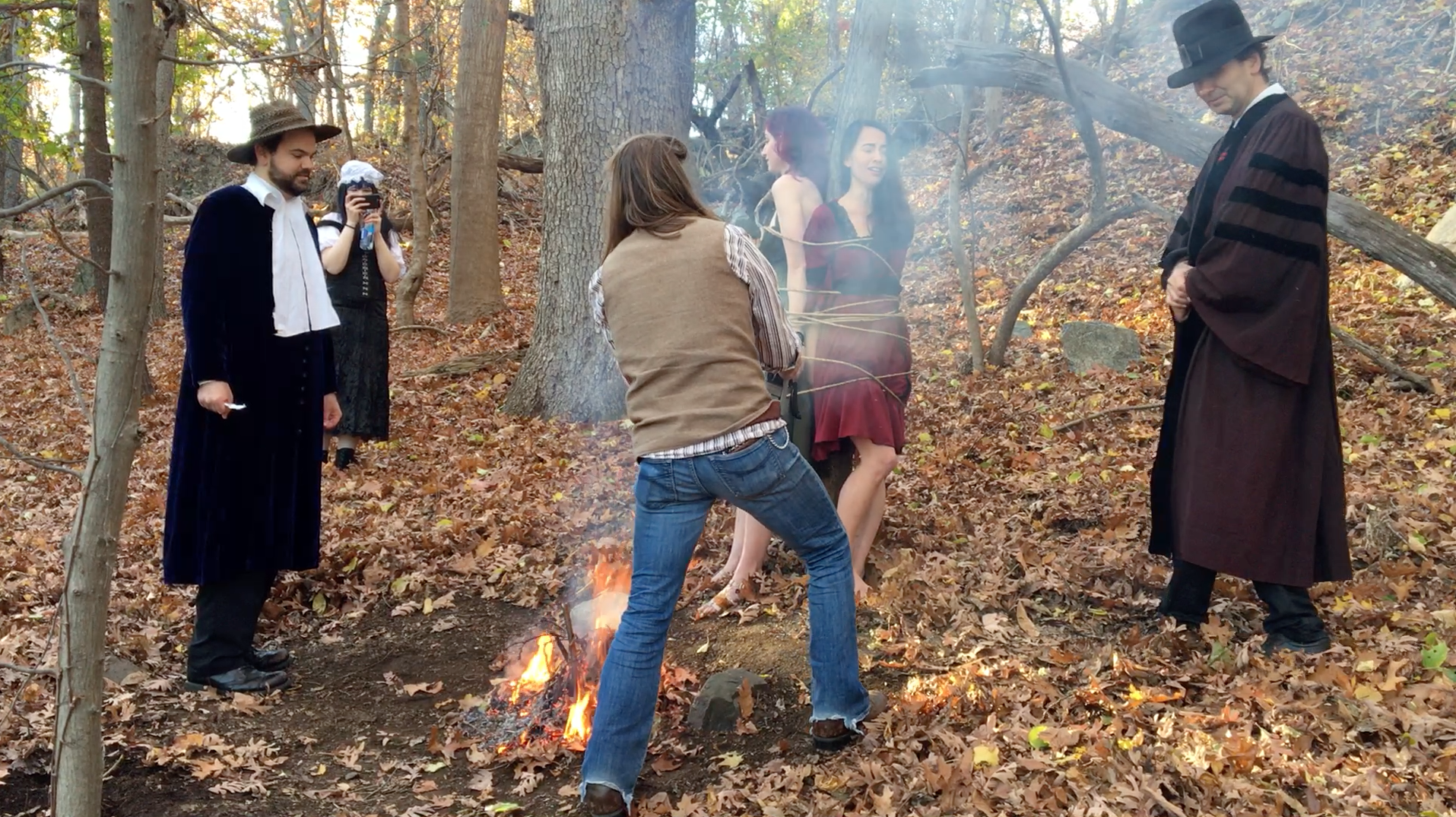 John Hartman of Reel Groovy Films on camera captures witches Geena Matuson (@geenamatuson) and Maya Simone burning at the stake. At back, Eve Xastur takes some photos while pilgrims Dawn Nightshade and Caleb Huntington bear witness.