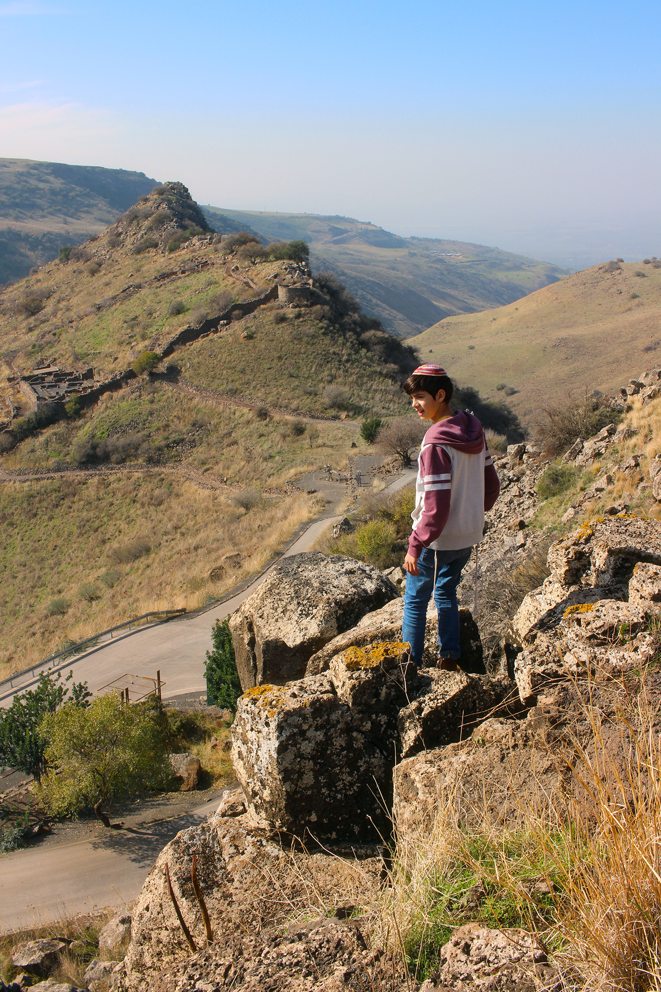 A boy stands atop a mountain of Gamla in Golan Heights, Israel. Photography by Geena Matuson @geenamatuson.