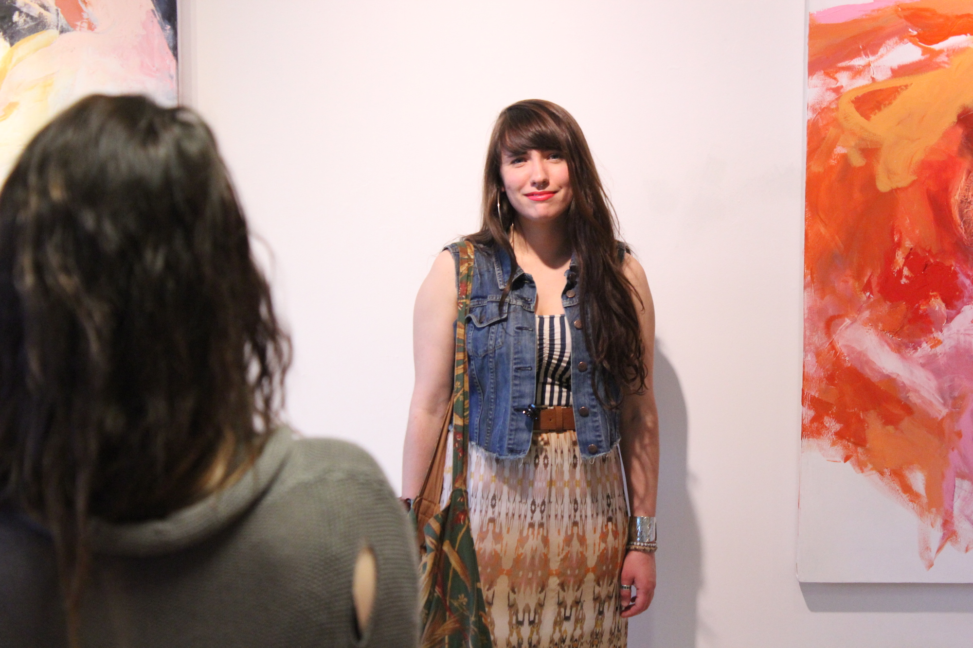 Carly Sheehan stands beside her paintings at Geena Matuson's (@geenamatuson) TransFIREmation Gallery Show & Installation in the MassArt Student Life Gallery, 2013.
