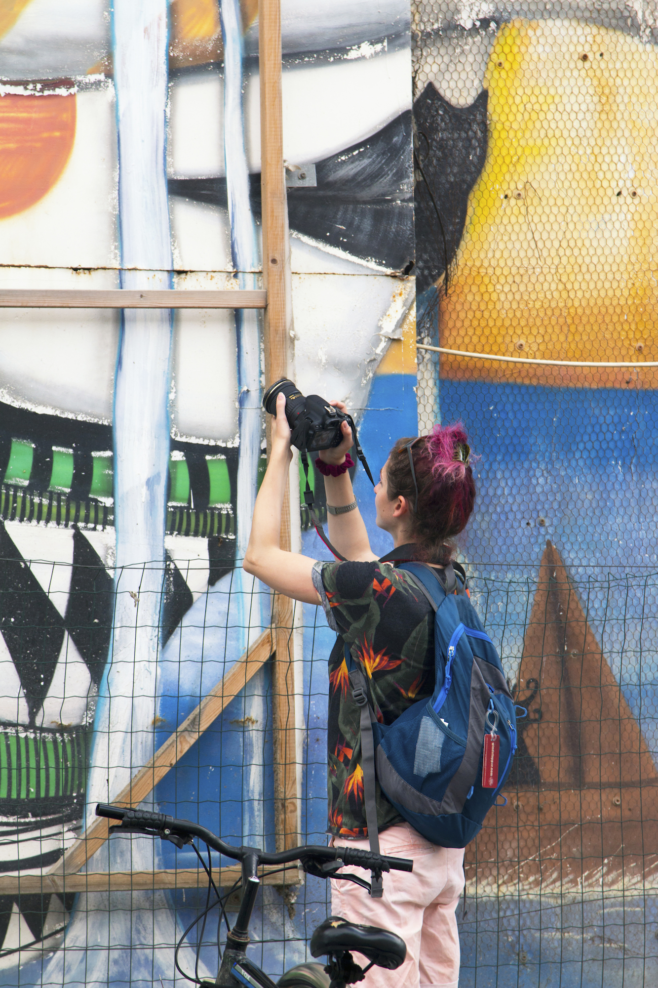 Geena Matuson photographing a wall mural in Tel Aviv-Yafo. See more #travel photography @geenamatuson #thegirlmirage at thegirlmirage.com.