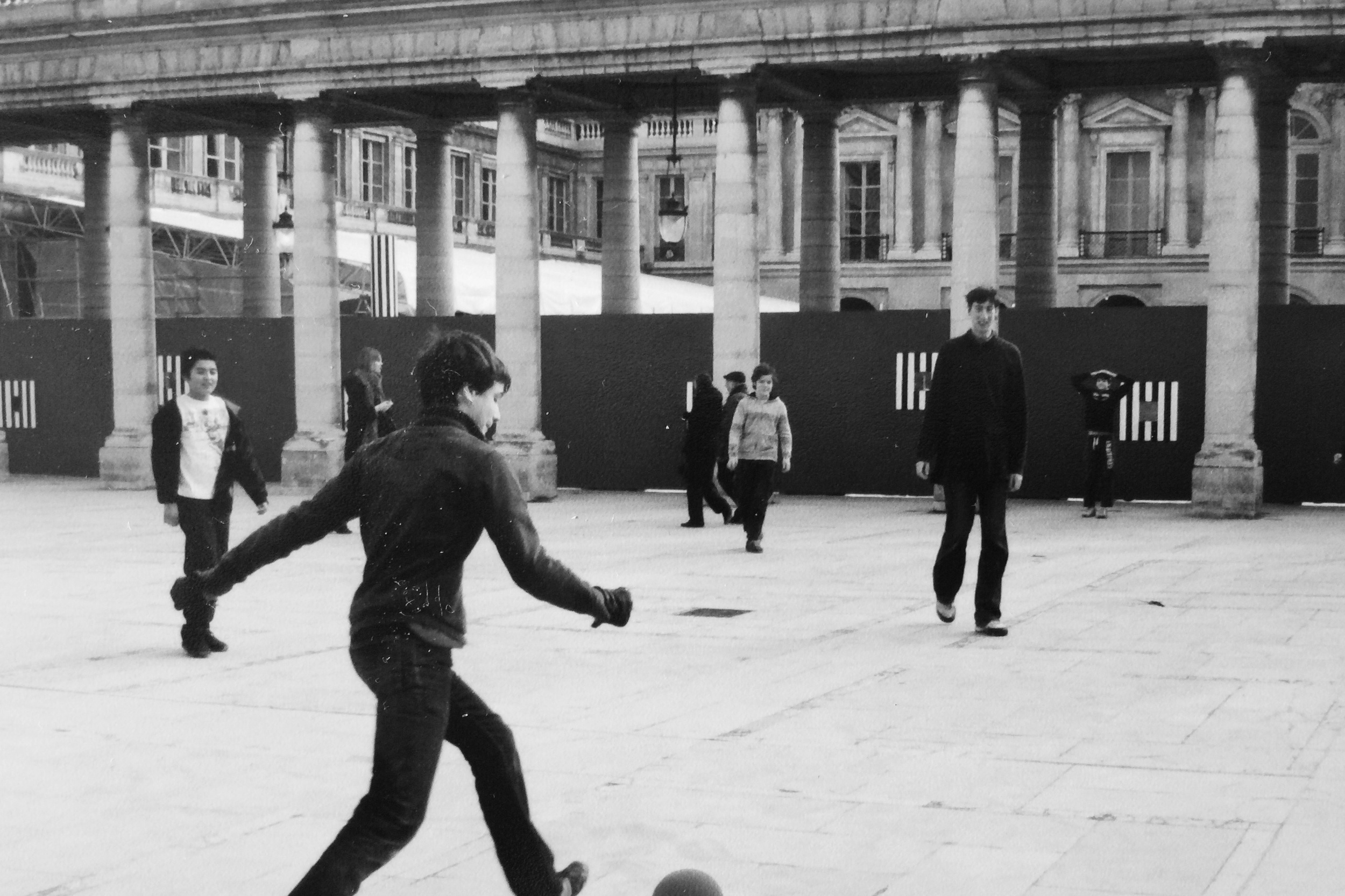 Boys playing kickball in Paris by Naomi Yamada