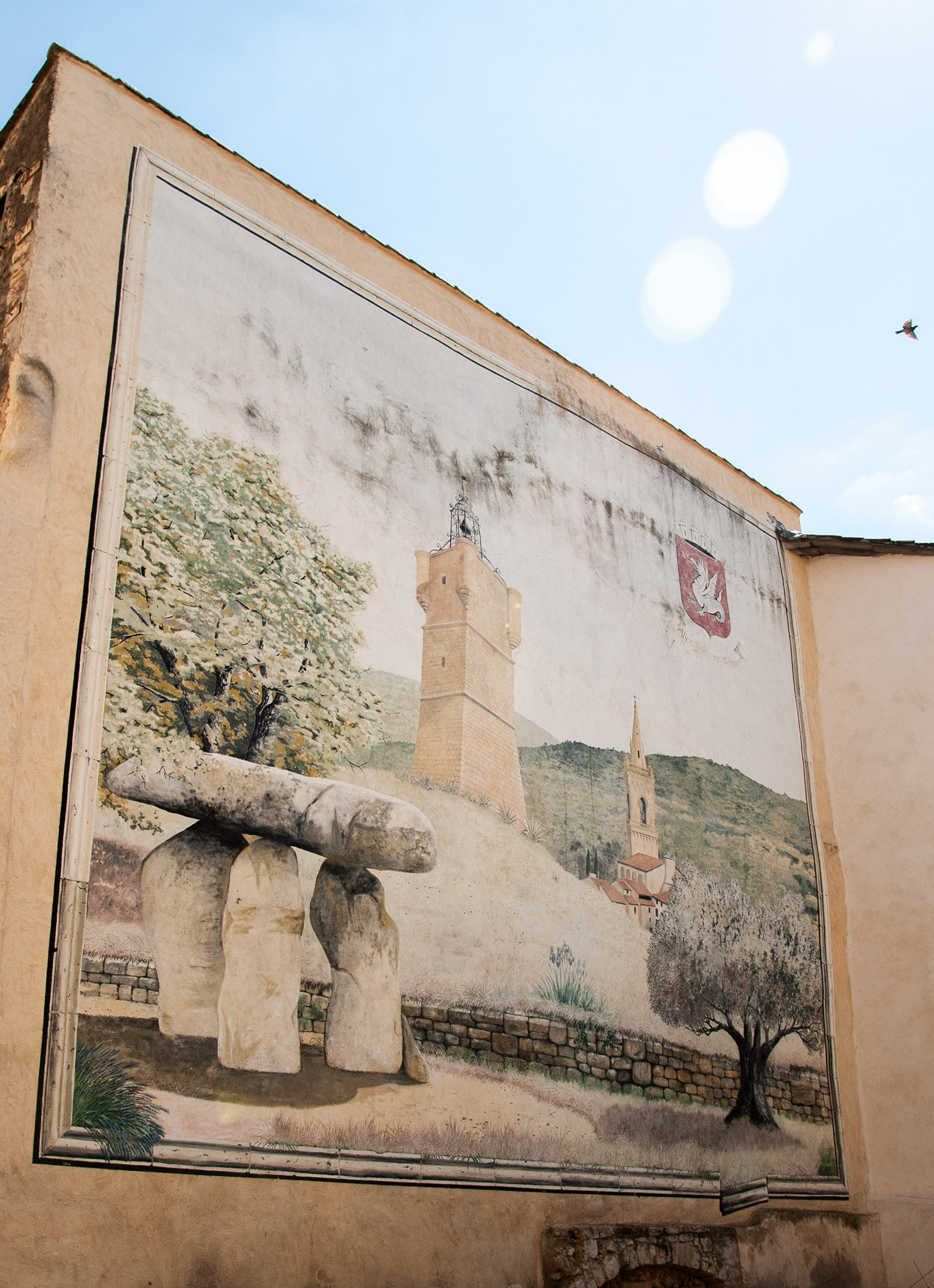 A mural in Draguignan, France, depicting a couple landmarks in the town, including the Dolmen Pierre de la fée, a Celtic structure on the bottom left, the clocktower, the church, and the red coat of arms in the top right.