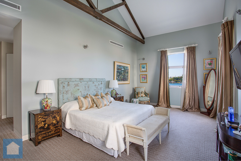 The exposed beams, high ceilings and styling all give this master bedroom loads of character and there's the bonus of amazing views of the river out every window.