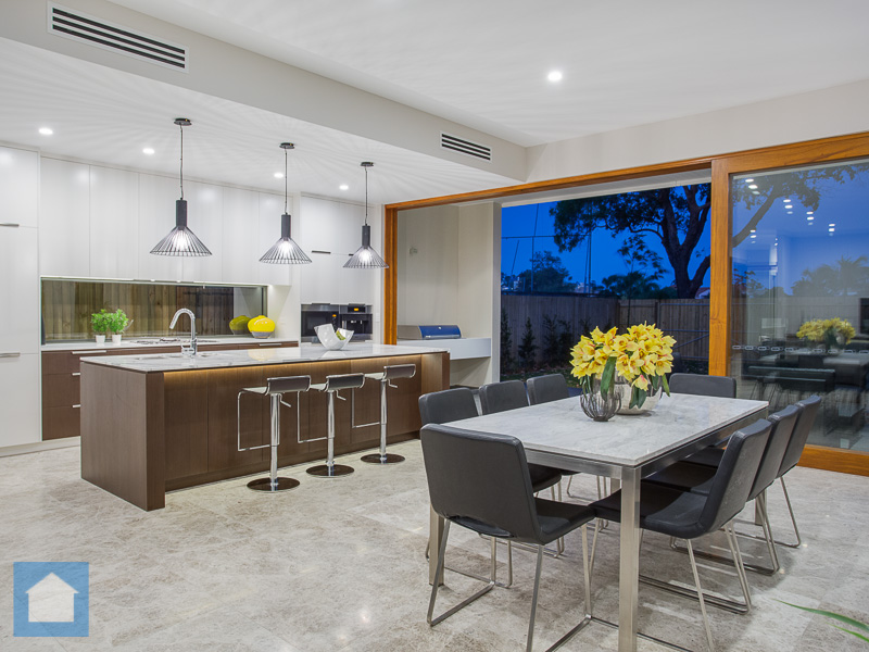 Island benchtop with glass splash back looking outdoors and fresh light marble tiles throughout.