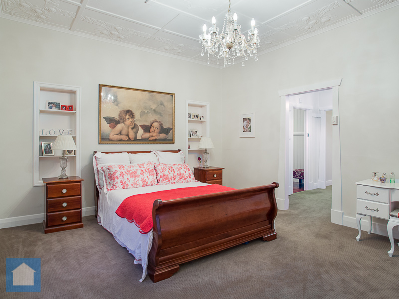 This very inviting master bedroom has such a style of it's own, with a beautiful chandelier hanging from the high ceilings that give this room a great sense of space.
