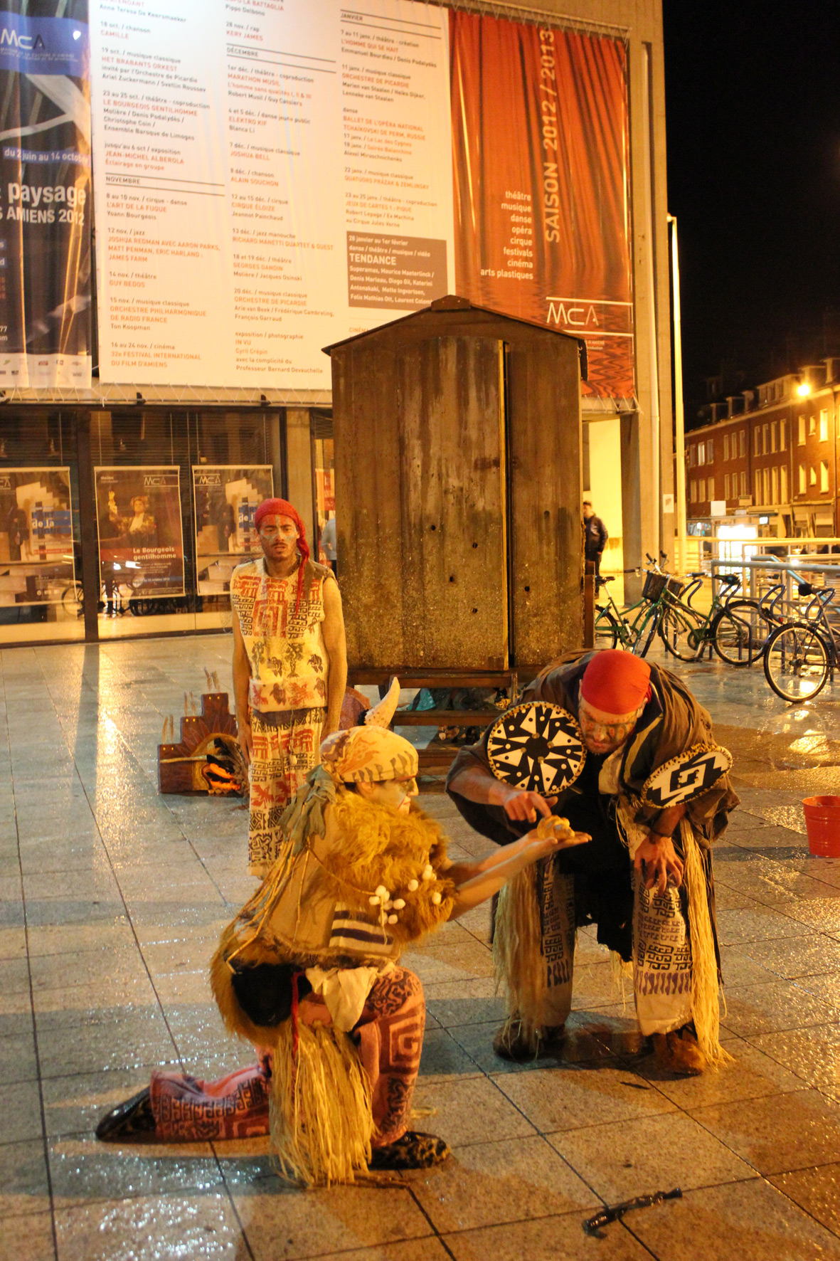 Terrible Shaman, Ulysses Black examines a croissant held aloft by fellow T.S. Annie Brooks with Howard Sivils looking on during a rain drenched Nuit Blanche in Amiens, France, 2012.