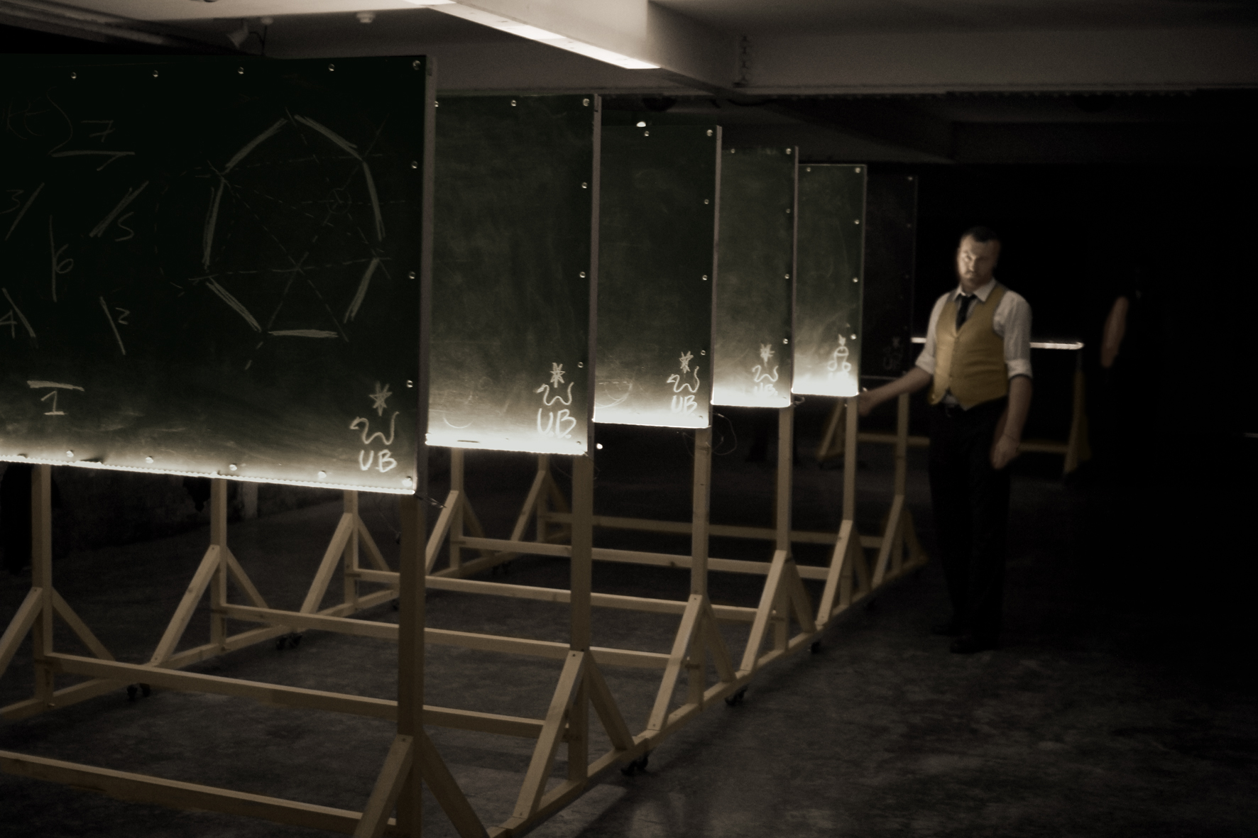 Ulysses Black, as Lecturer 1, reveals the presence of the linear sequence of blackboards within the first configuration. Performance at the Basement, Brighton 2013