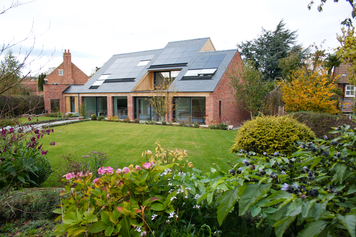 The south facade, designed to maximise winter solar gains while providing shading in summer, . Photovoltaic panels and rooflights are integrated into the slate roof.