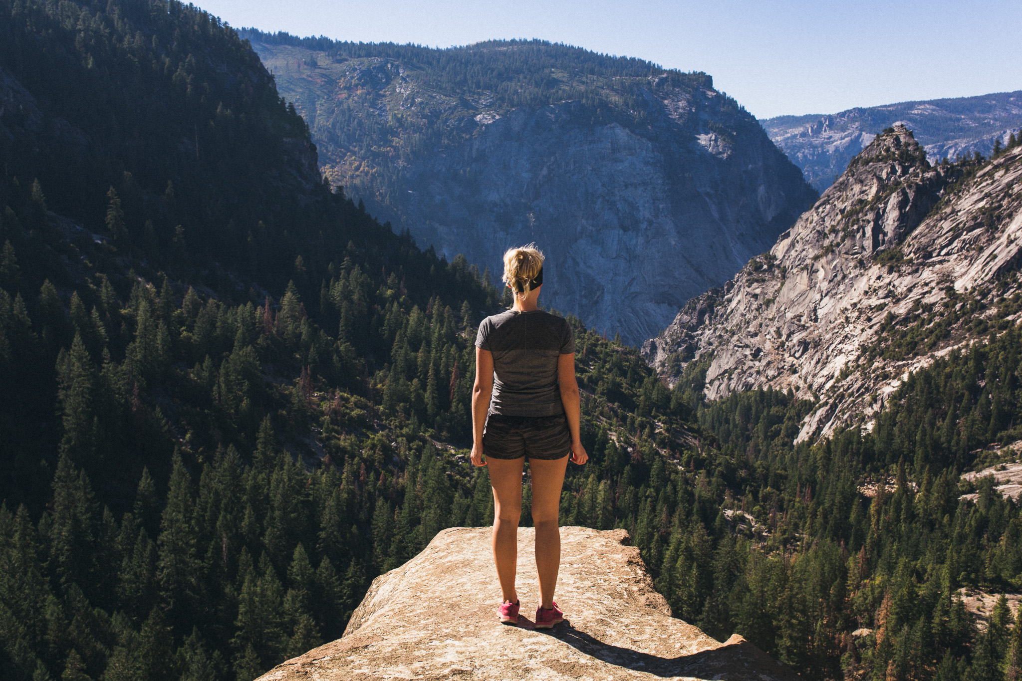 Girl-standing-dangerously-on-cliff-edge