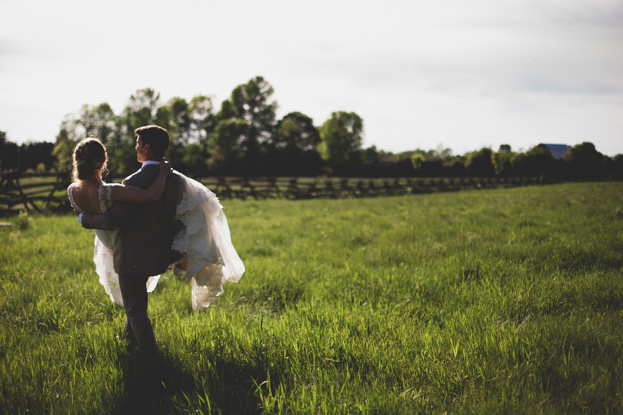 38-Groom_carrying_bride-through-field.jpg