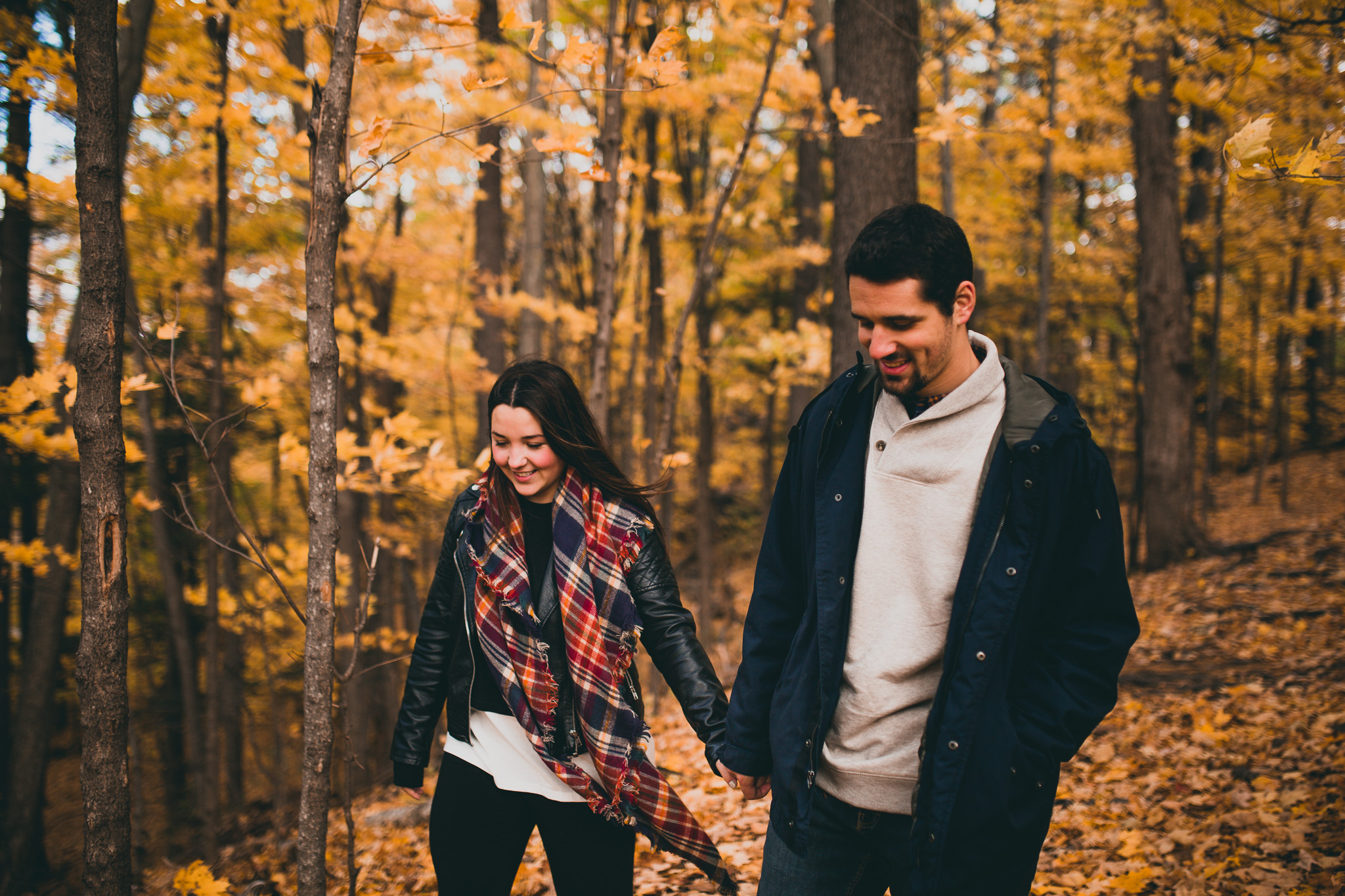 couple walking through fall leaves