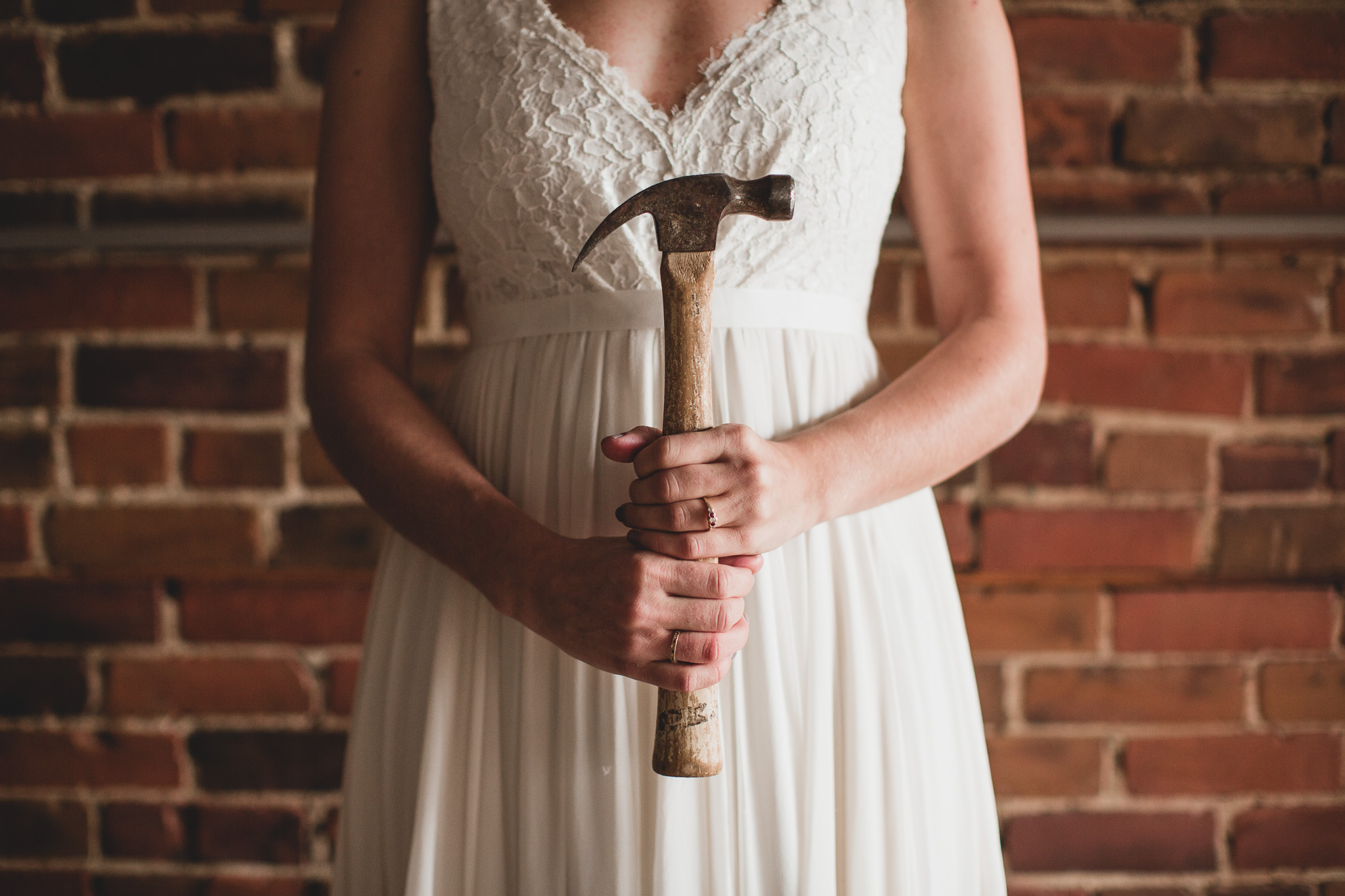 Woman in a Wedding Dress holding a hammer