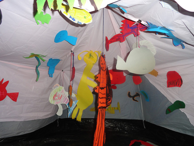 """A tent transformed into an open-mouthed whale during the """"Belly of a Whale"""" ART BRAINS project at Artisphere. The students filled the whale's belly with cut-out drawings of objects and creatures they imagined the whale had swallowed. Click here to read more about this project ."""