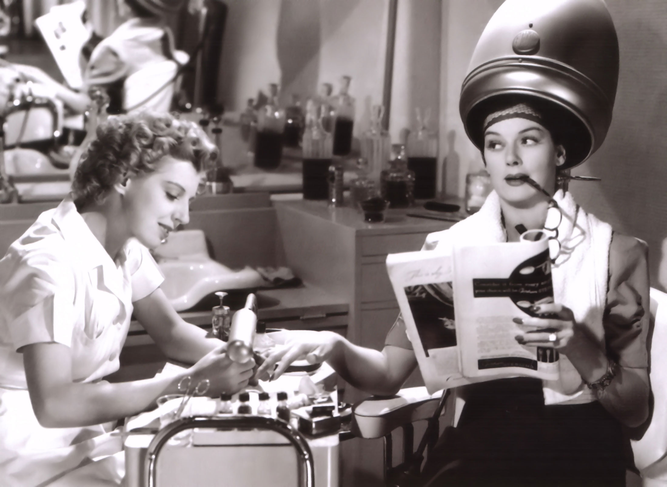 Scheming Rosalind Russell engages in a bit of malicious gossip at the beauty parlor with the manicurist played by Dennie Moore.