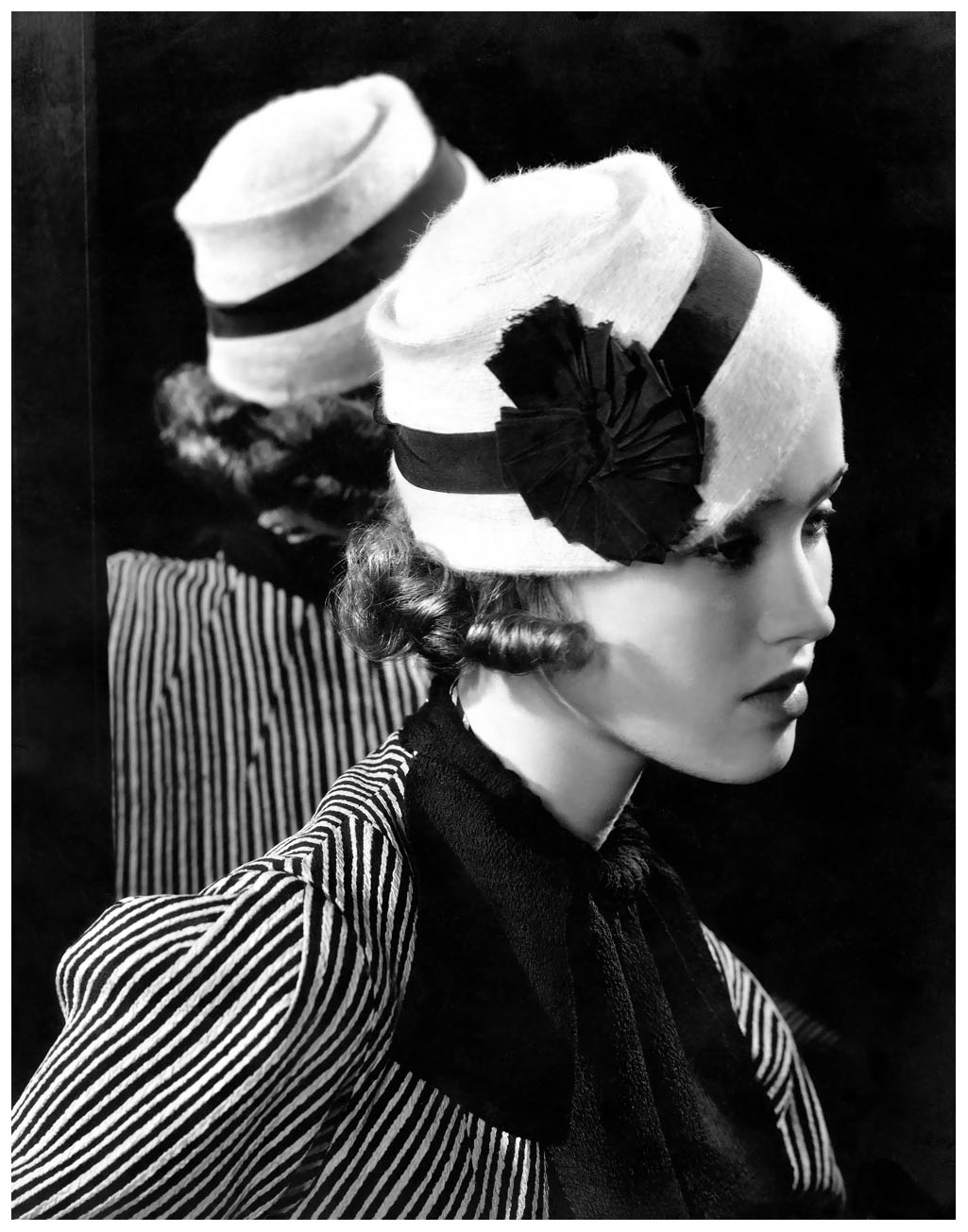 Mary Taylor wearing white angora hat with grosgrain band by Maria Guy, striped rough silk ensemble, and dark shirred scarf, with reflection in mirror behind her 1933