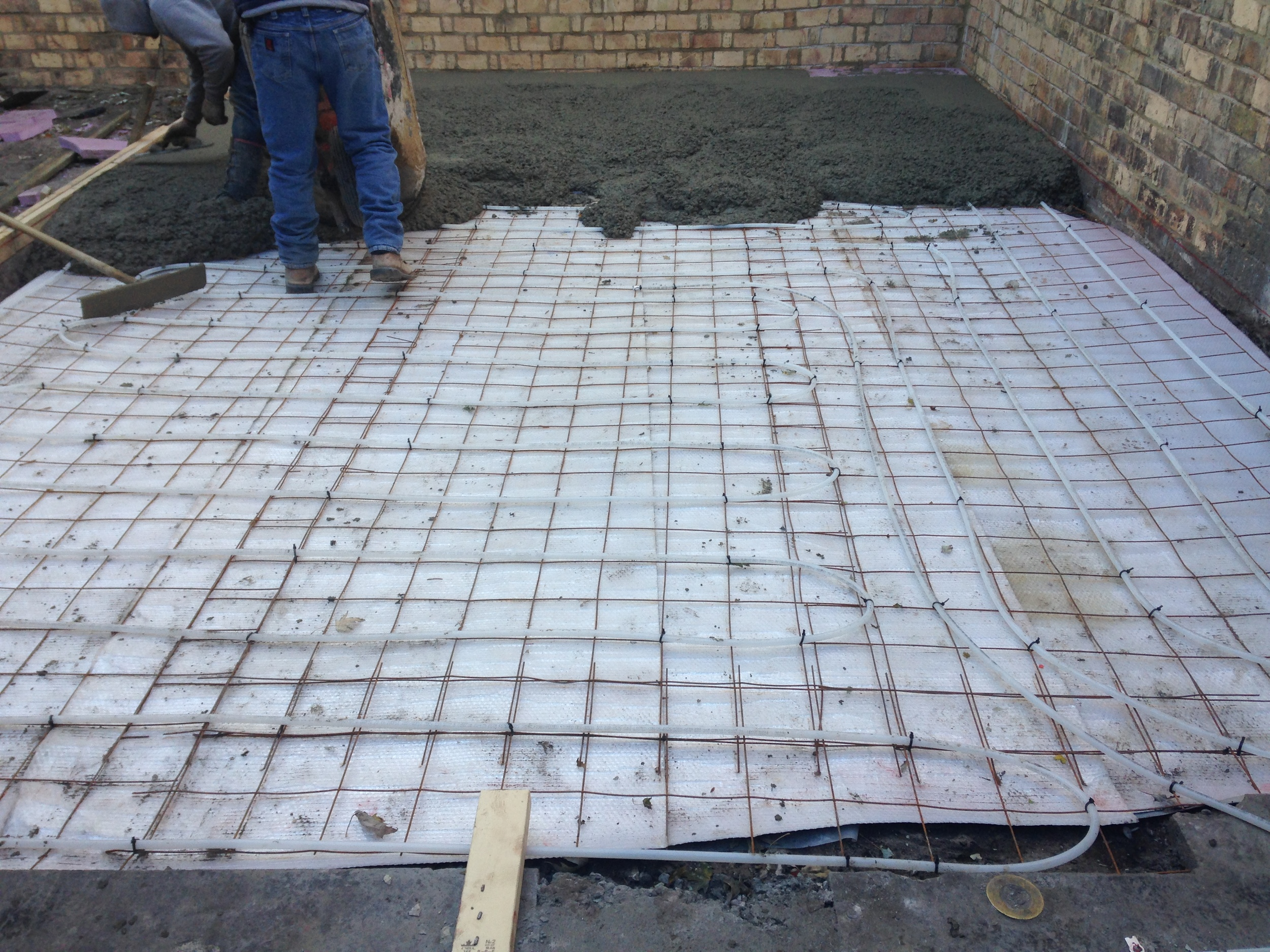 pouring the new slab in the family room over the radiant heating tubes