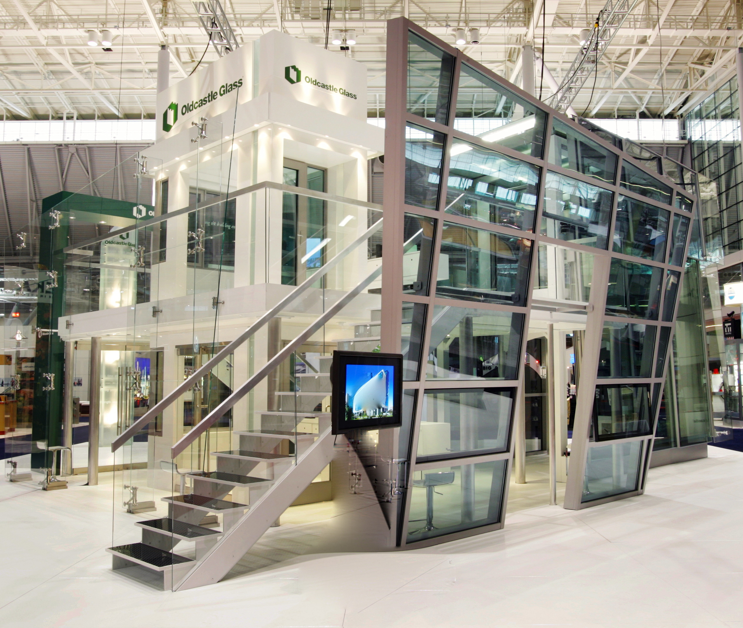An earthquake-resistant, double-deck, glass and aluminum trade show exhibit. Structural elements, glass tower framing assembly, product displays, and graphics by Ndio. Design by Design Collaborative.