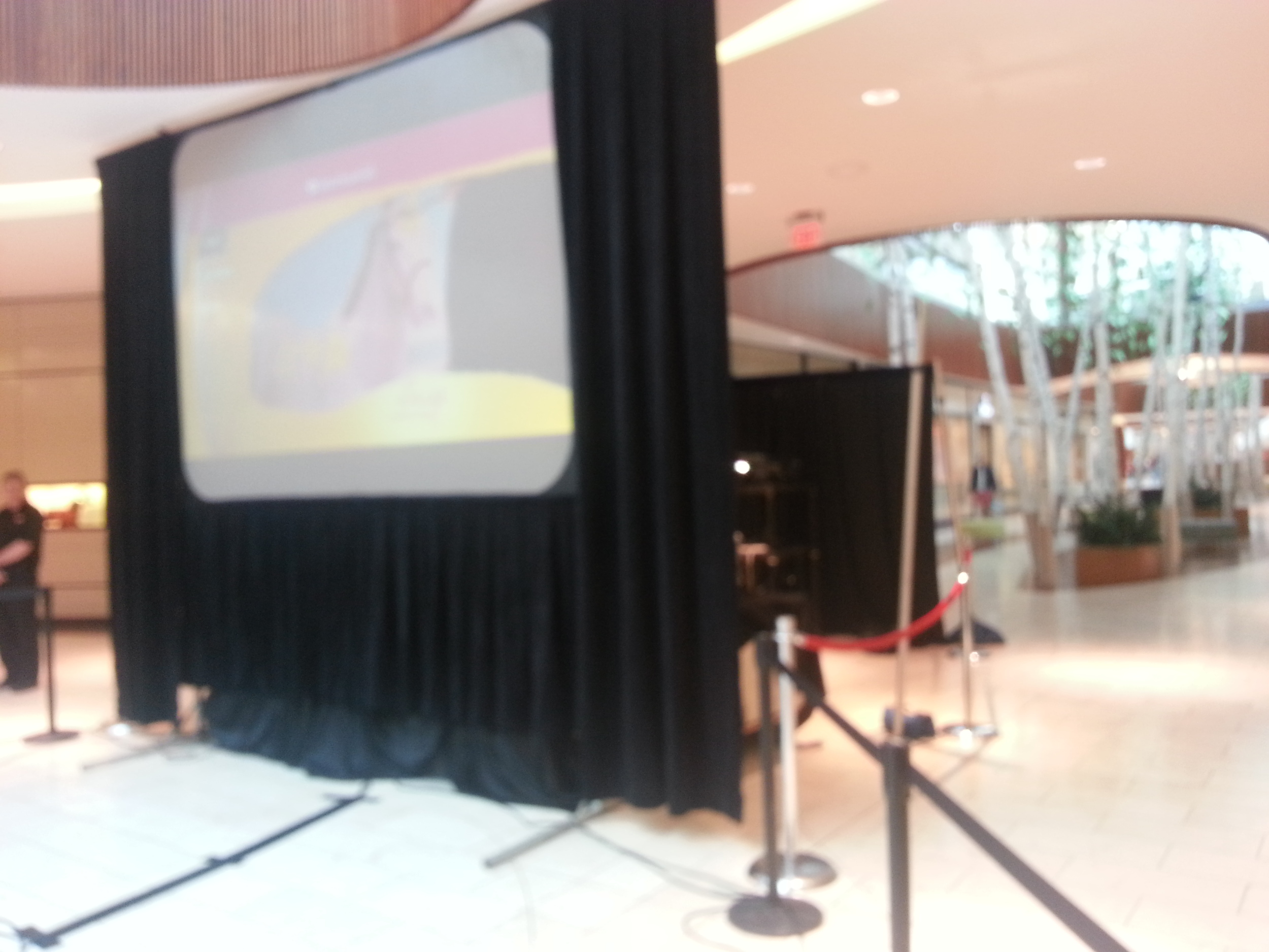 A slightly blurry camera phone picture of the screen, projector and PA system being set up at the Natick Collection.