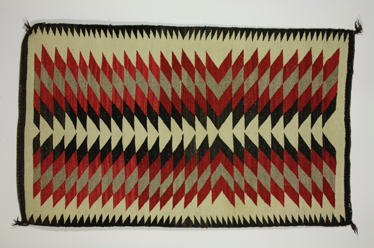 Navajo Germantown Eye Dazzler Rug: Rectangular woven rug; red, grey, and black integrated diamond design on a natural colored field with black border; small black knotted tassel on each corner.  /  Science History Institute . / 2008, Gregory Tobias.