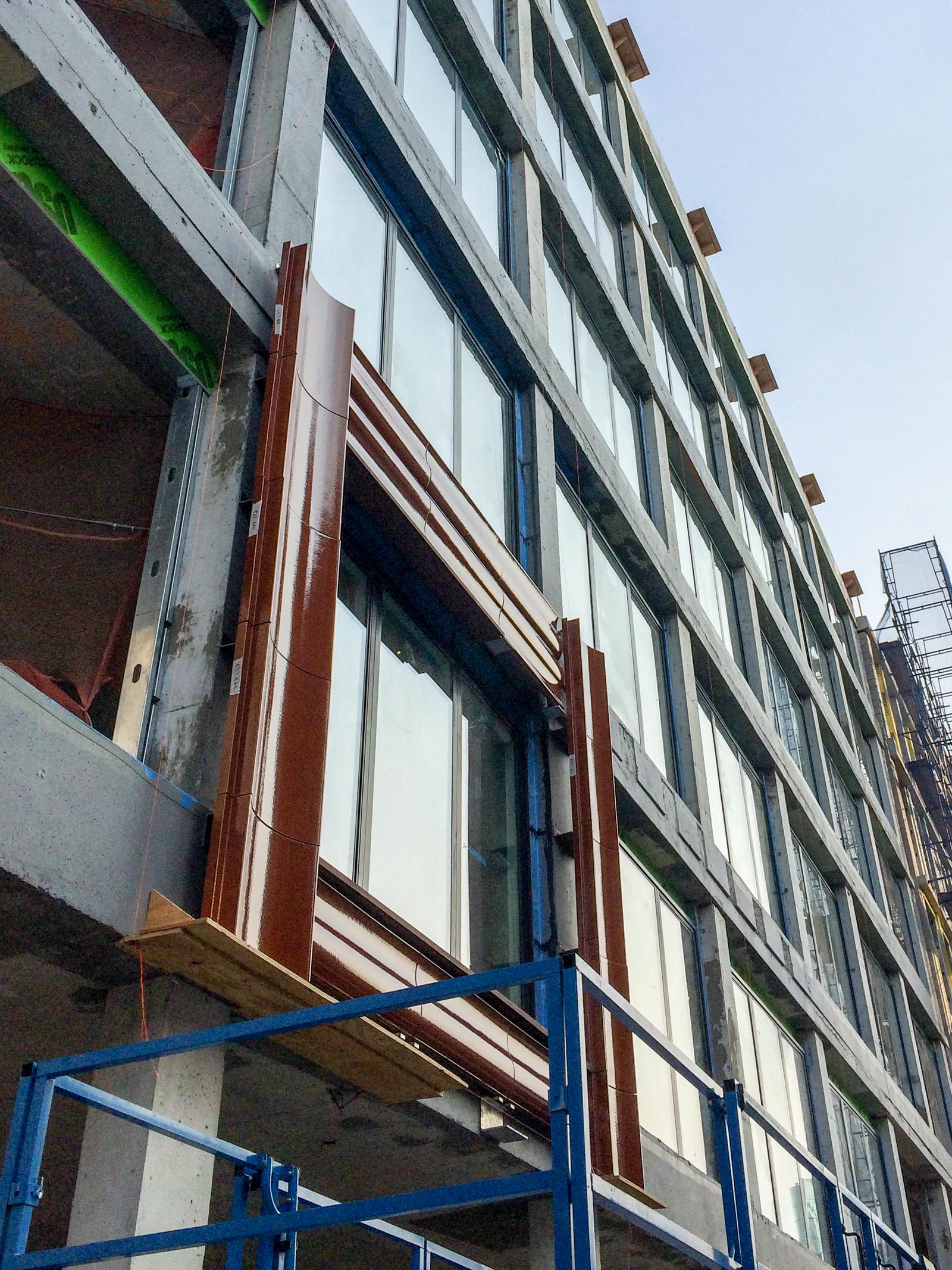 Terracotta panels installedaround a second floor window.